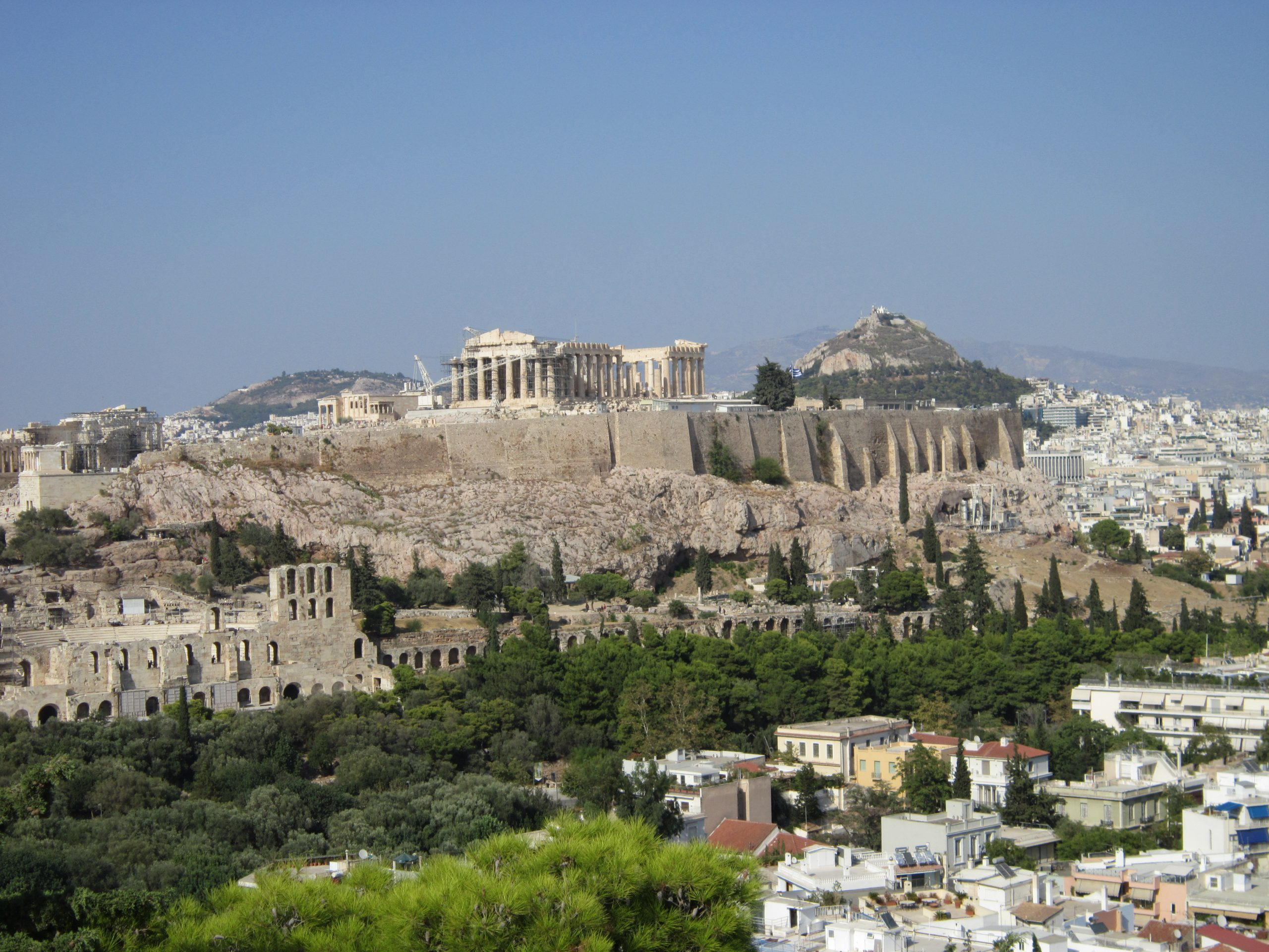 A view of the Athens Acroplis with woods and building sin the foreground and Mount Lycabettus in the background.