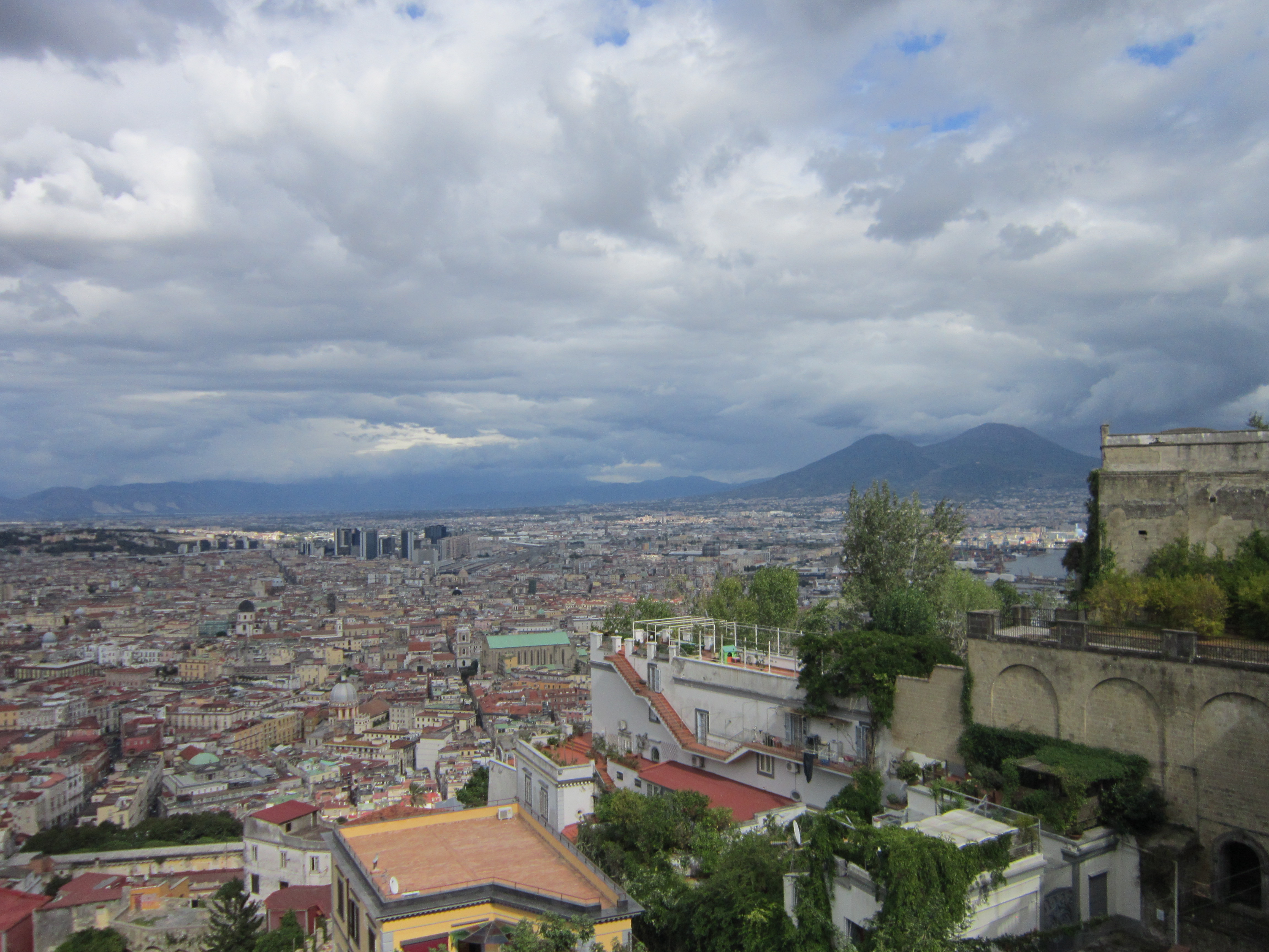 A view across the city of Napoli, with a cloudy sky and the Mount Vesuvius volcano in the bacground