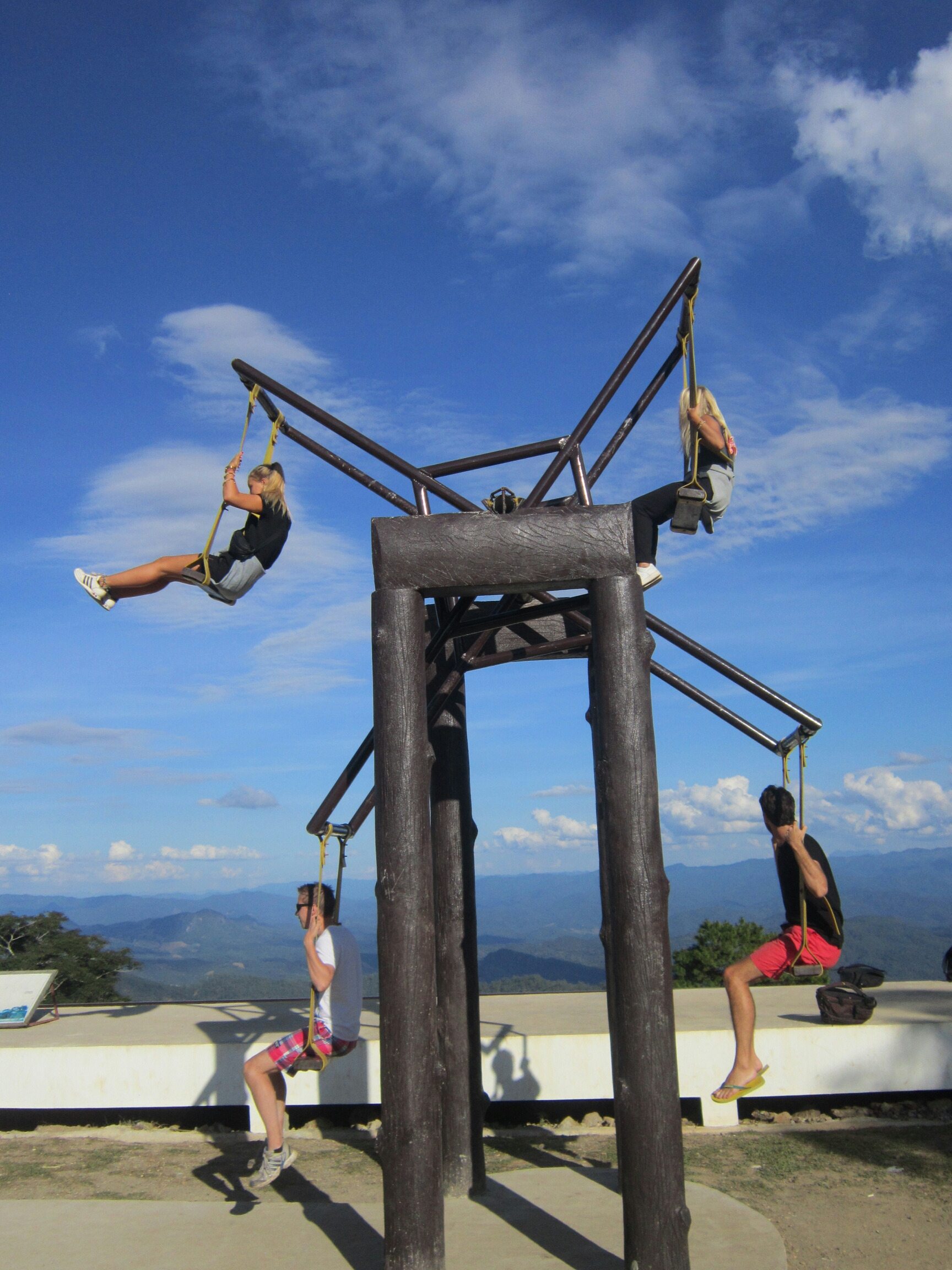 4 people on the giant swing at Pang Mapha Viewpoint, with blue sky and clouds behind them.