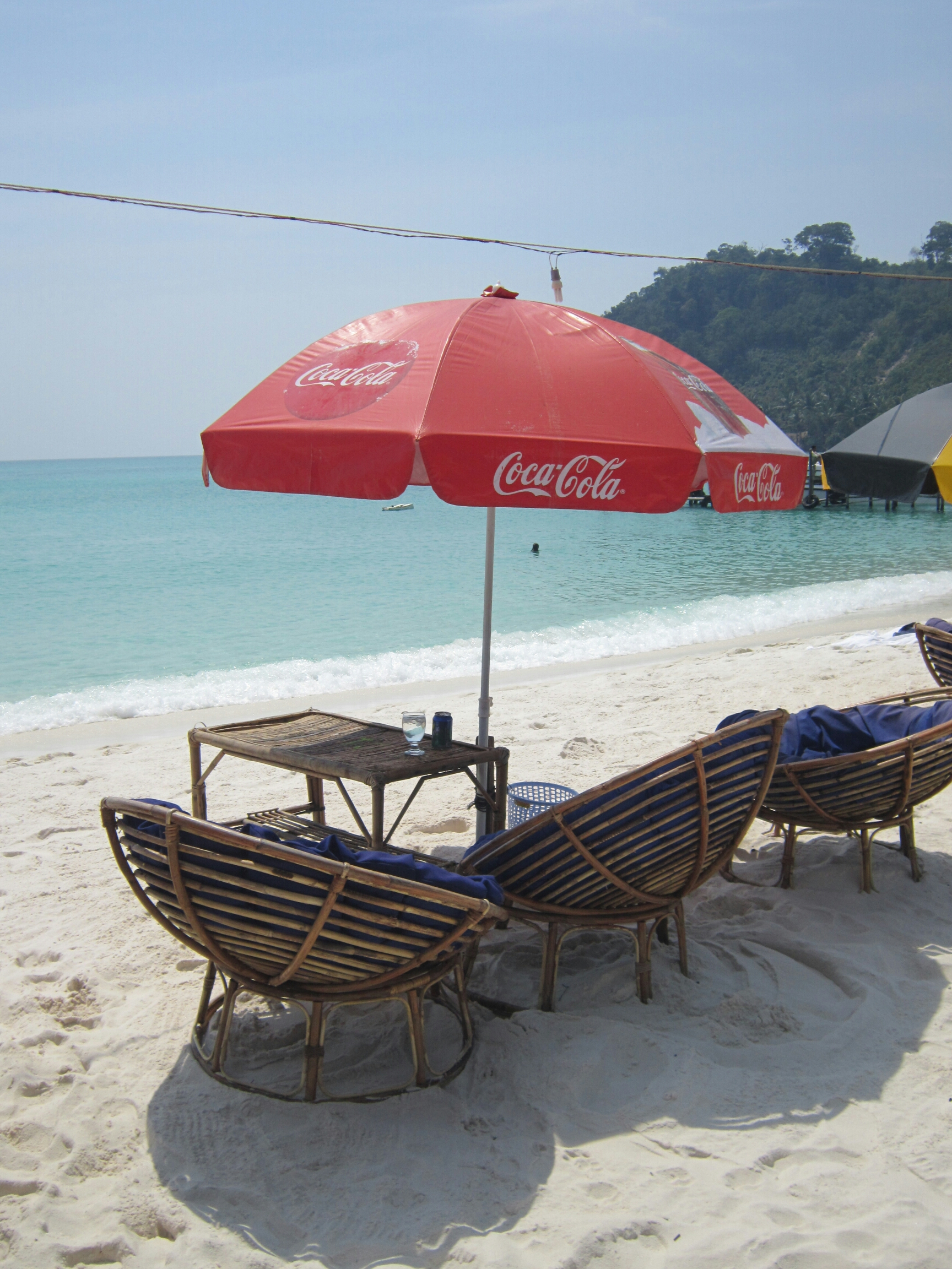 backpacking tips - slow down! Table and beach chairs with sun umbrella on Koh Rong, Cambodia