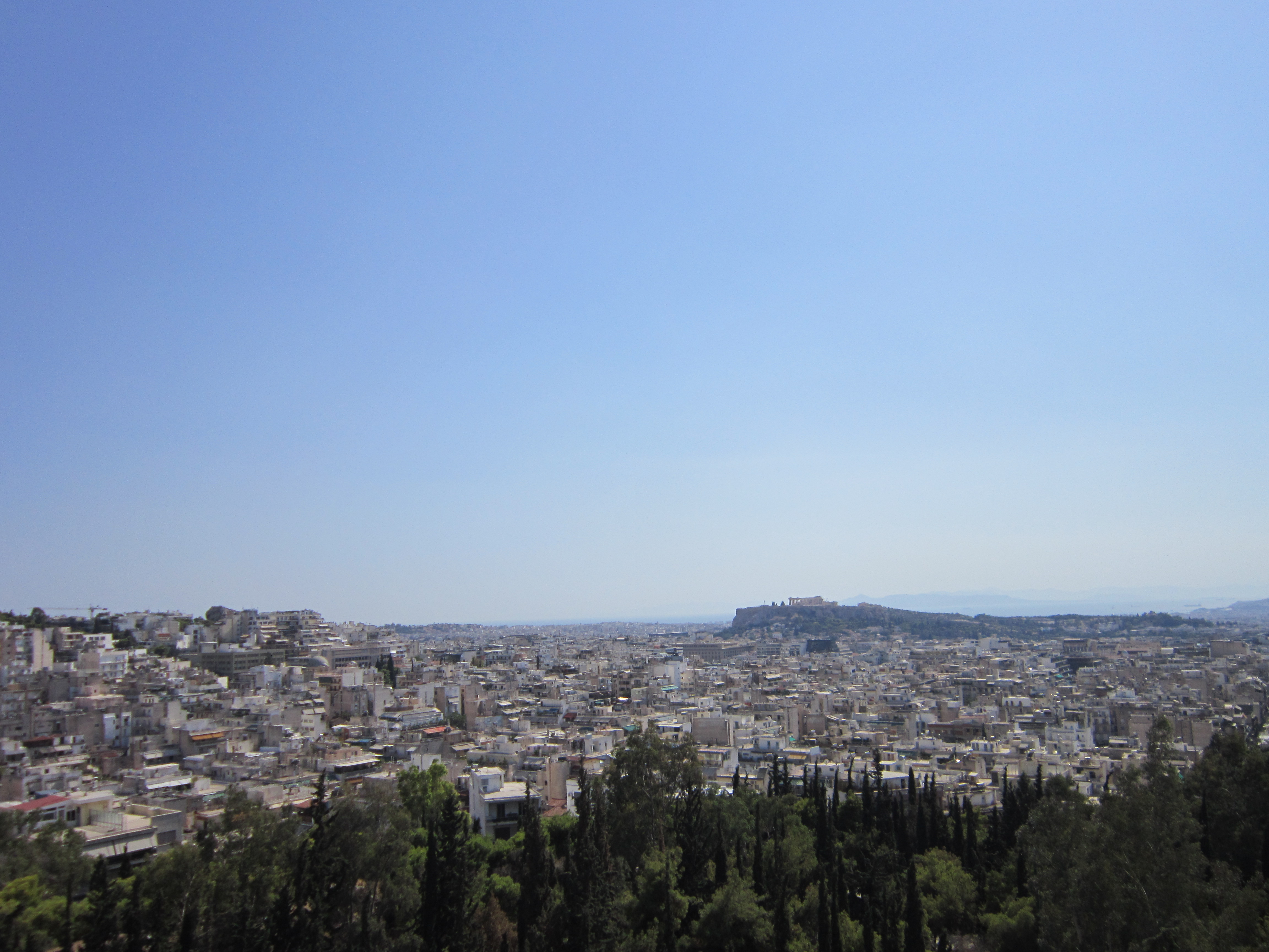 A view over the city of Athens with bright blue skyses above