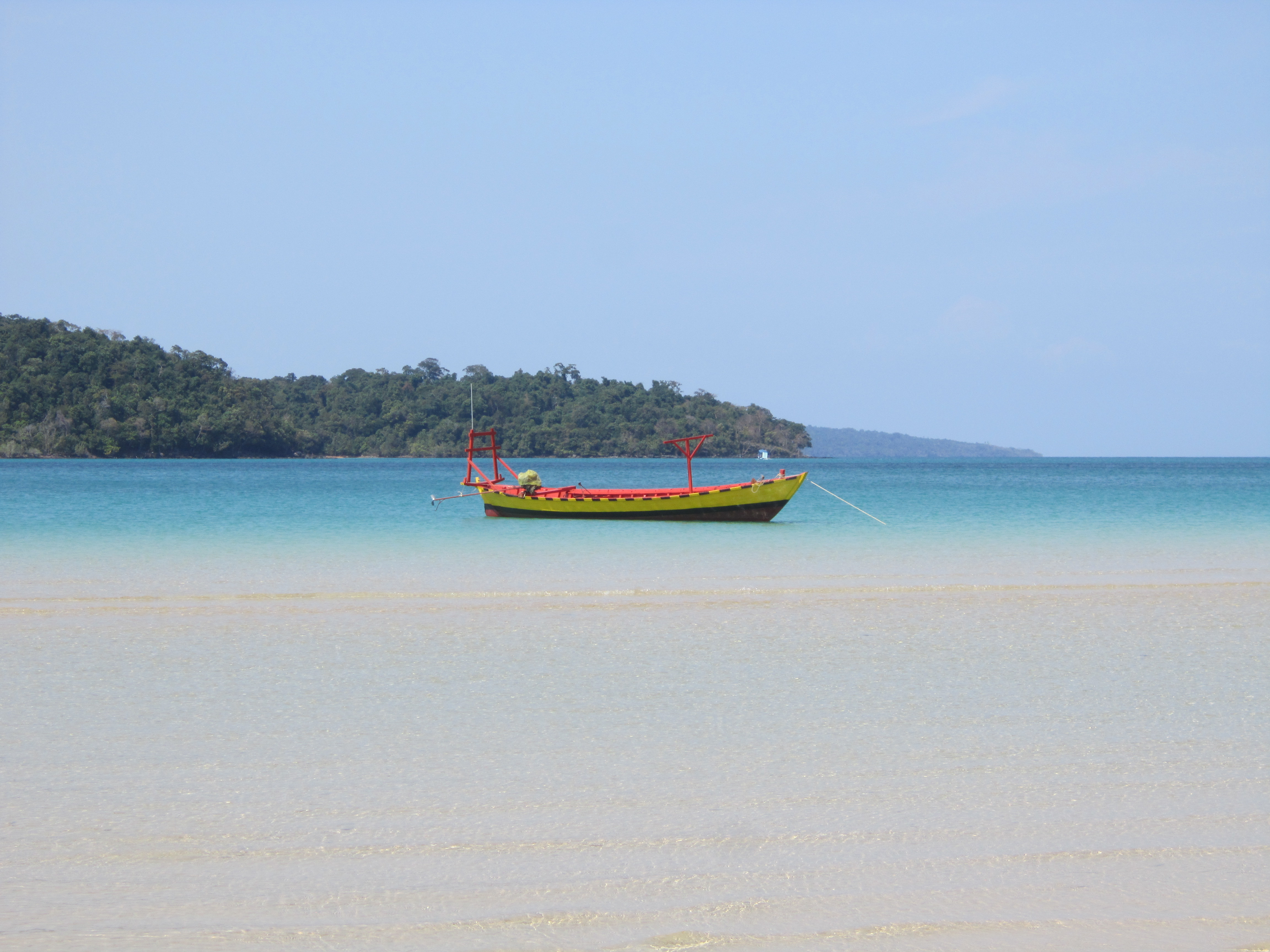 Boat on blue water with sand in the foreground. M'pai bay, Koh Rong Sanloem, Cambodia