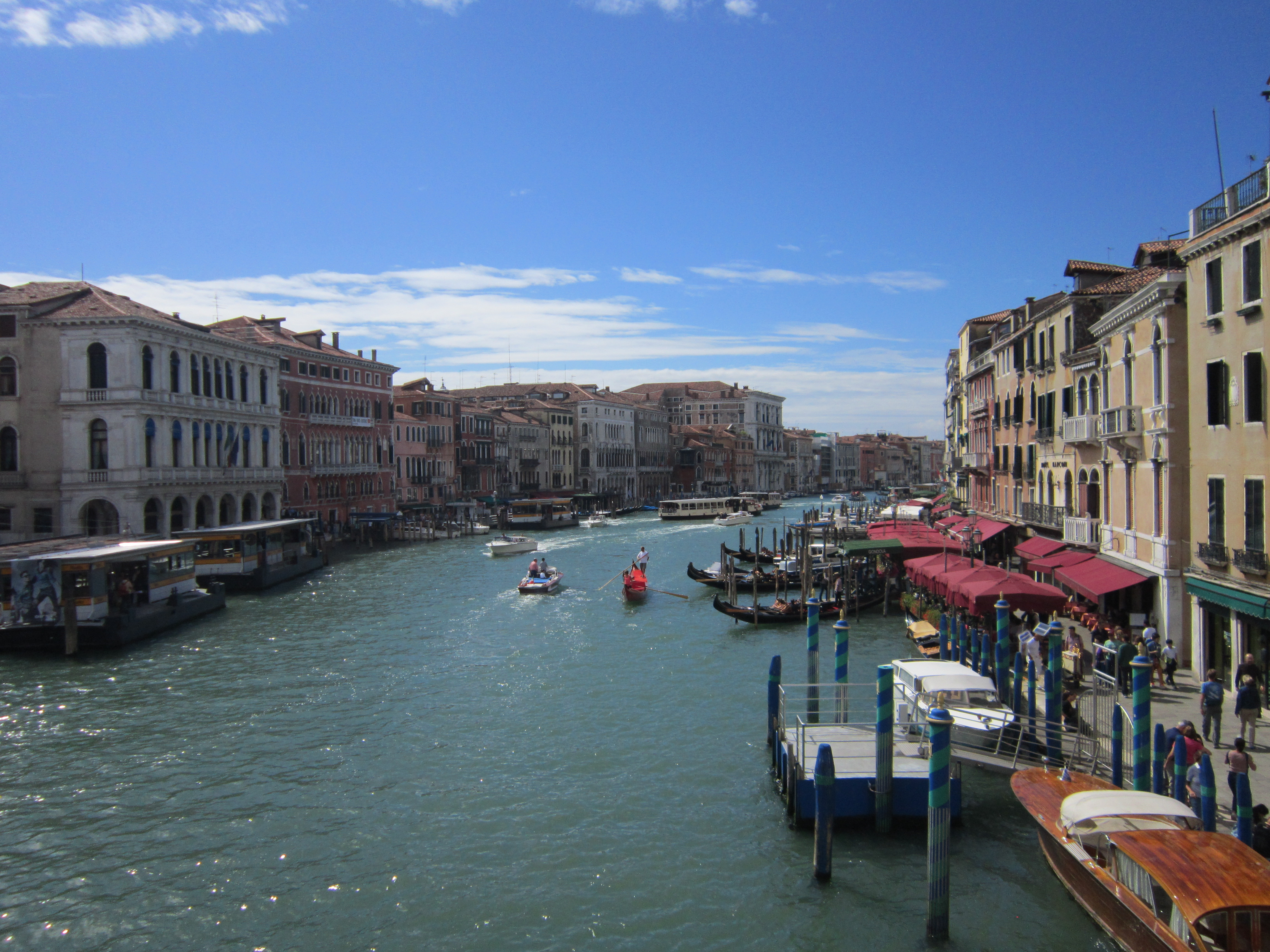 A view of Venice on a sunny day,  one of the major destinations of this Italy backpacking itinerary. Boats moved along the large canal in the background