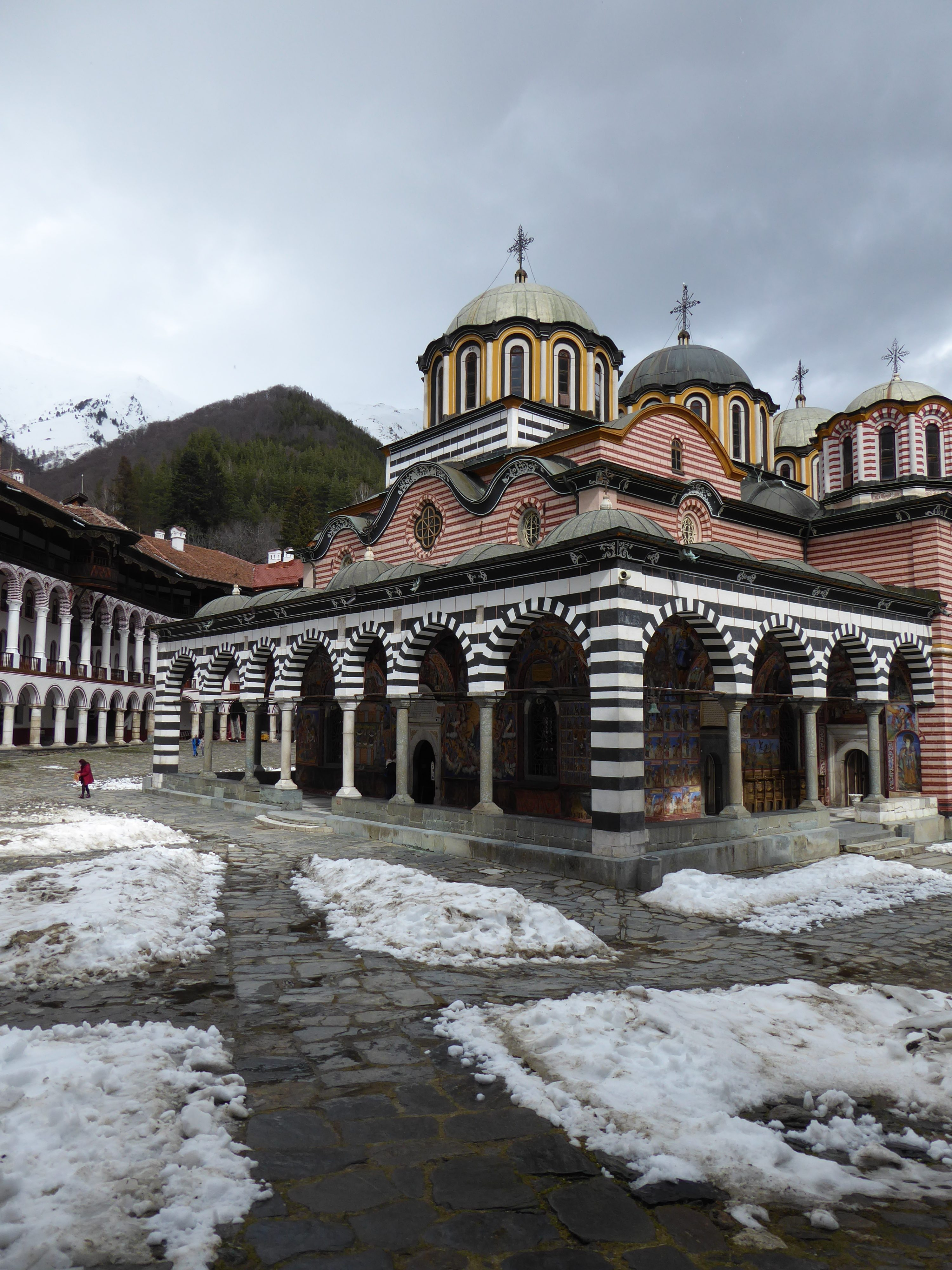 View inside Rila Monastery, buildings, mountain in distance, snow still on gorund 2 hours from Sofia, Bulgaria