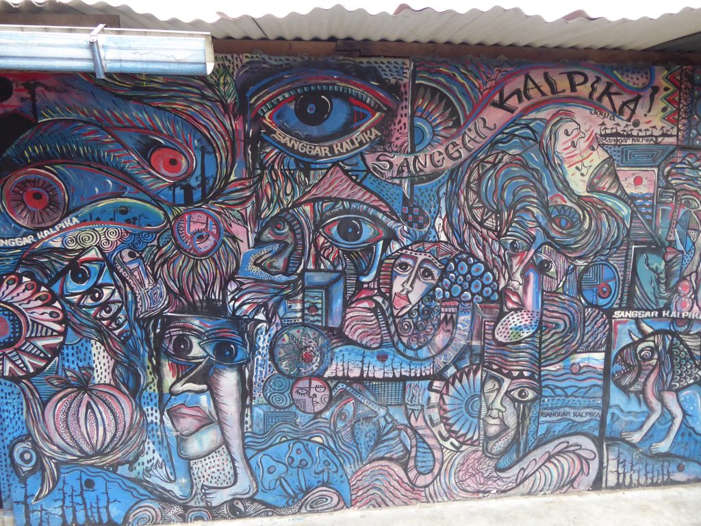 Street Art near to Taman Sari, inside the Kraton - patterns using blue and pink as main colours including multiple faces