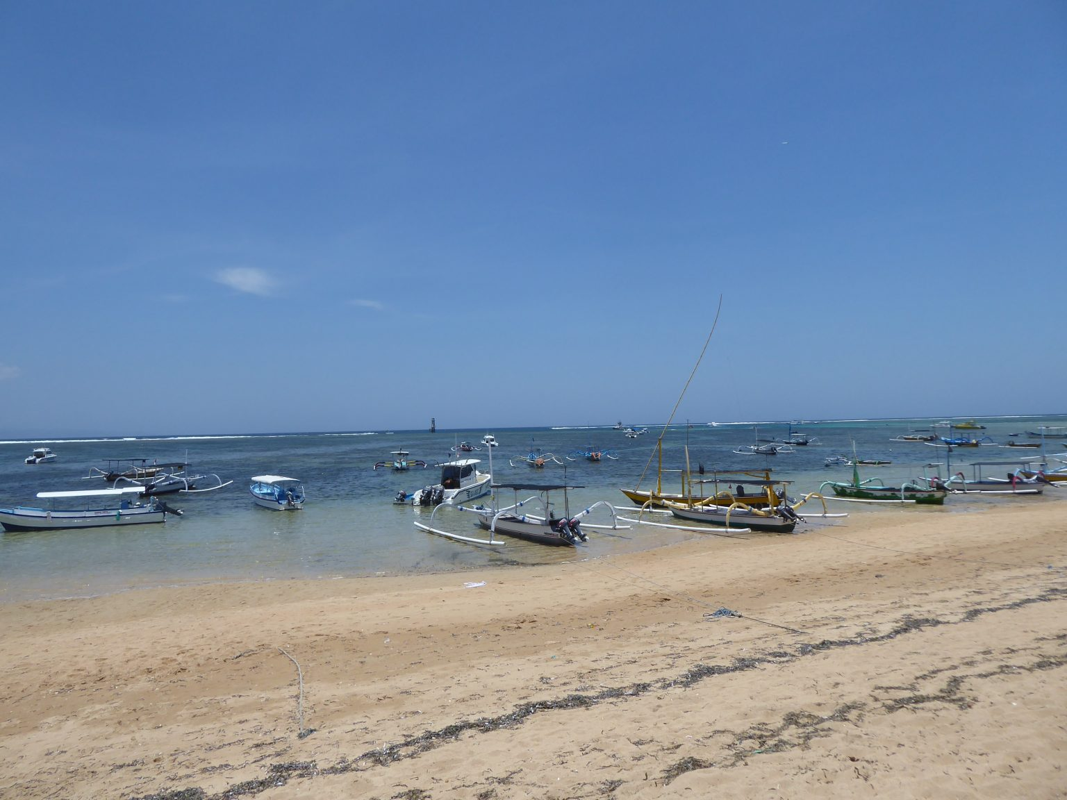 Sanur Beach with boats parked in the water - Backpacking Bali