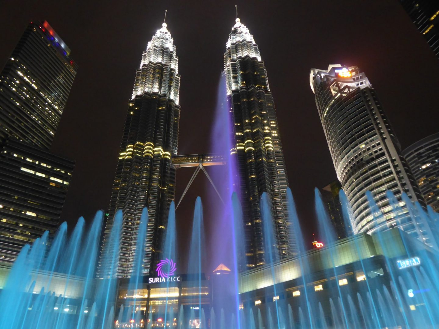 The Petronas Twin Towers in the evening - including water show lit up light blue