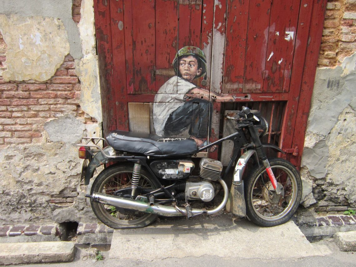 Artwork of boy riding a motorbike. The motorbike is real and attached to the wall to look like the boy is riding it.