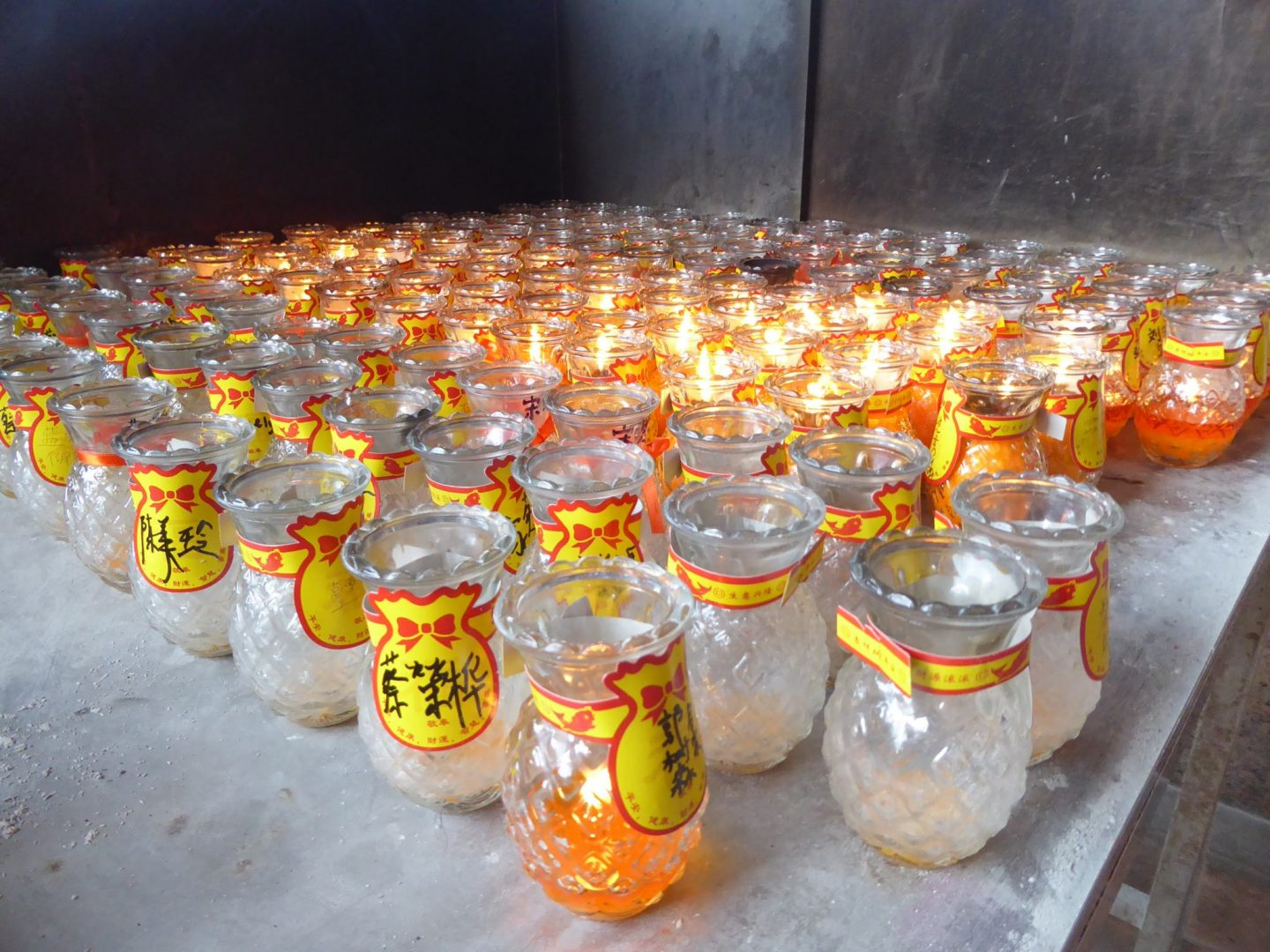Buddhist candles burning. many candles inside glass with chinese lettering on the outside.