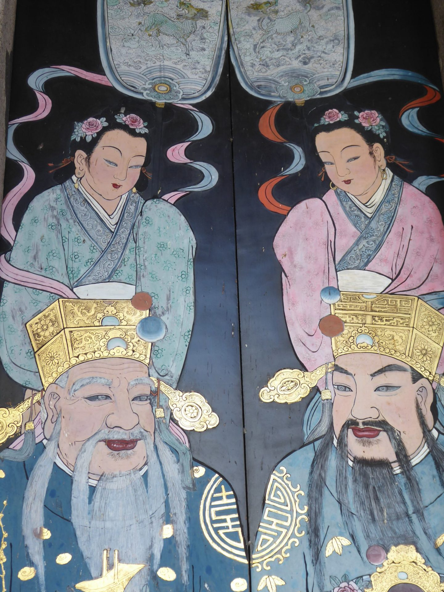 Illustrations at the Penang Teochew Association temple - 2 men and 2 women in traditional Chinese dress on a dark background - the women are situated behind the men with decorations above them- Penang Travel Guide