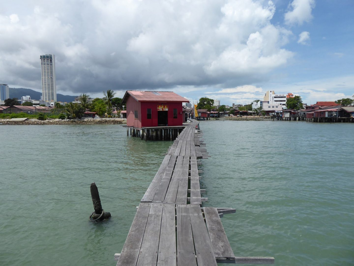 Looking back down Tan Jetty. A narrow path above the water with a small building on the left, painted red.  The mainland in the background - Penang Travel Guide