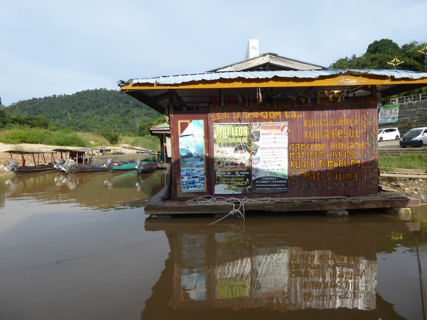 Graffiti style writing on sid eof building floating on river. Offer travel destinations.