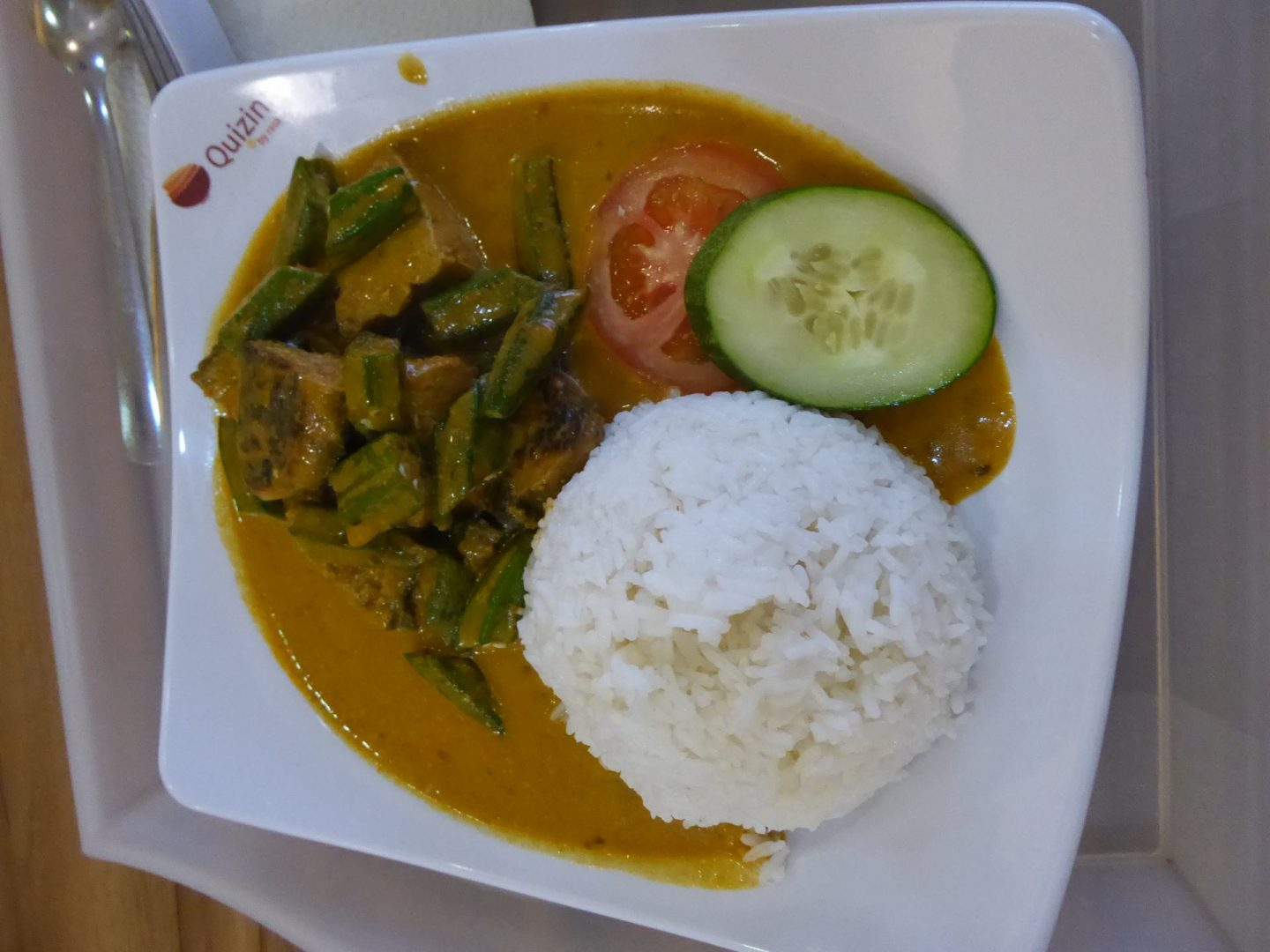 Malaysian curry in a bowel, including rice, tomato, cucumber