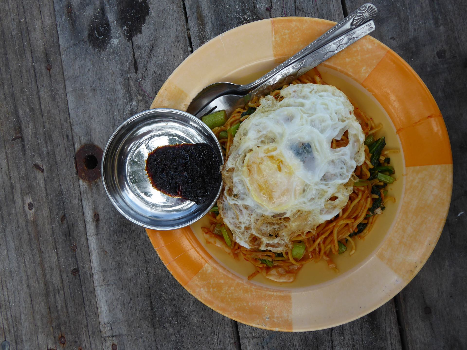 A plate containing Mee Goreng with fried egg, Including a small metal pot with chilli spice