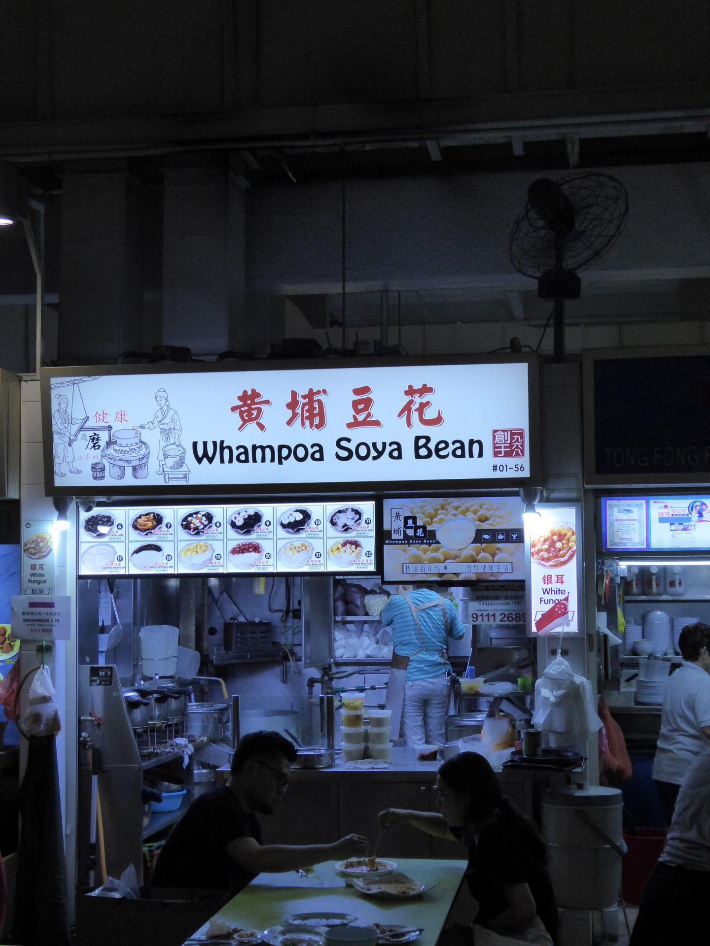 The Whampoa Soya Bean Stall. Table with people eating in the foreground.