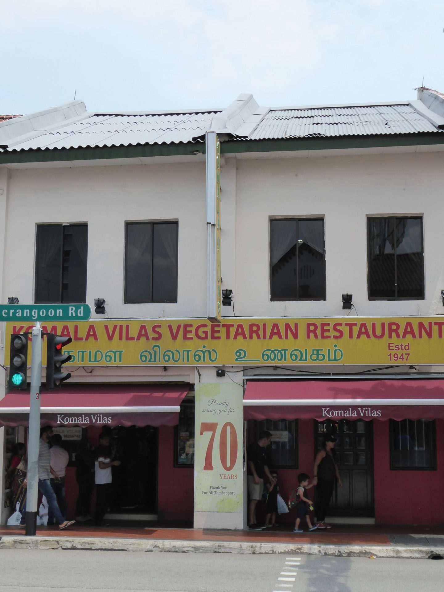 A photo the outside of Komala Vilas on Serangoon Road in Singapore. A yellow sign stretcher along above the restaurants identifying it in English and Tamil.