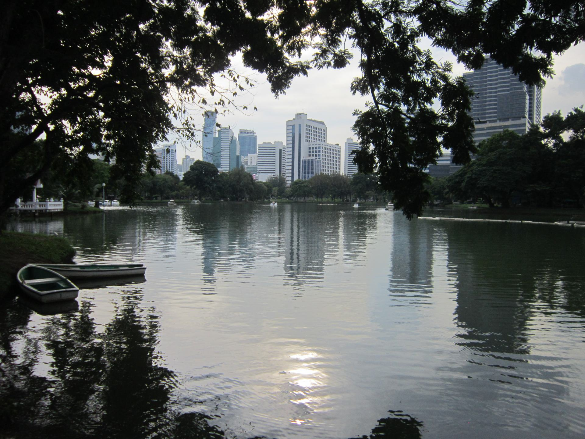 A view across a lake in Lumphini park, surrounded by trees with skyscrapers in the distance. The sun is reflecting on the water.