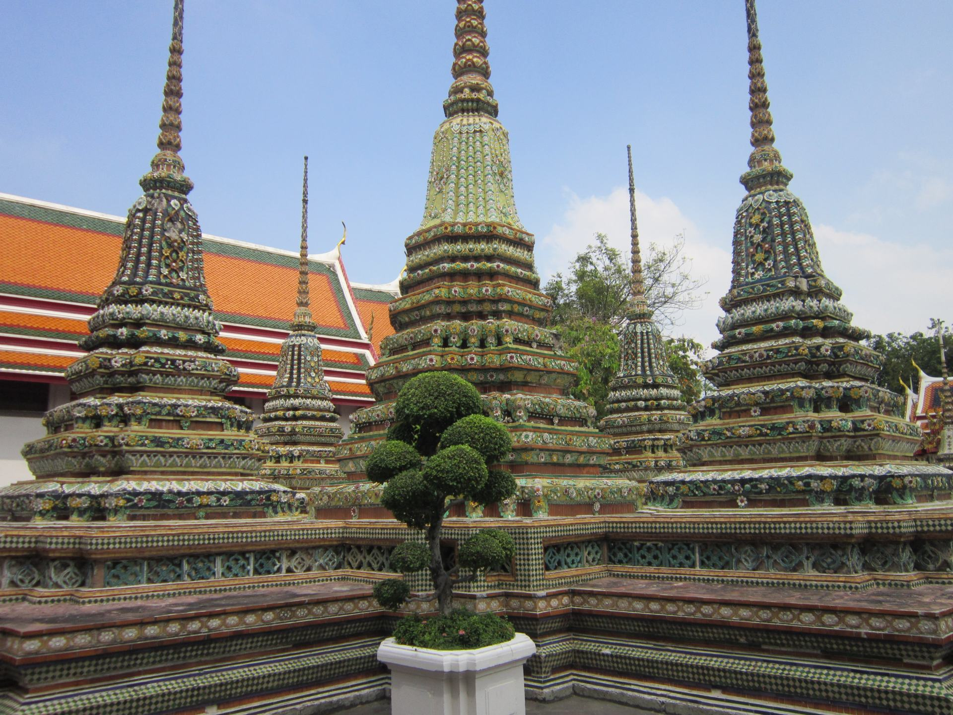 Multi coloured stupas at Wat Pho in Bangkok, one of the fantastic Cities in Southeast Asia. 3 in the foreground, 2 in the background. A small tree in front of them.