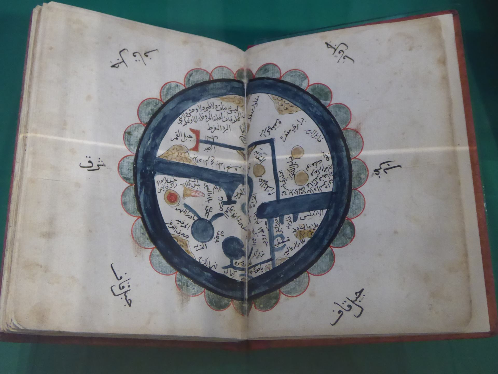 An Islamic map across the centre of 2 pages of a book. On display in the Islamic Art Museum in Malaysia. It has the best display of Islamic art of all the museums In Southeast Asia.