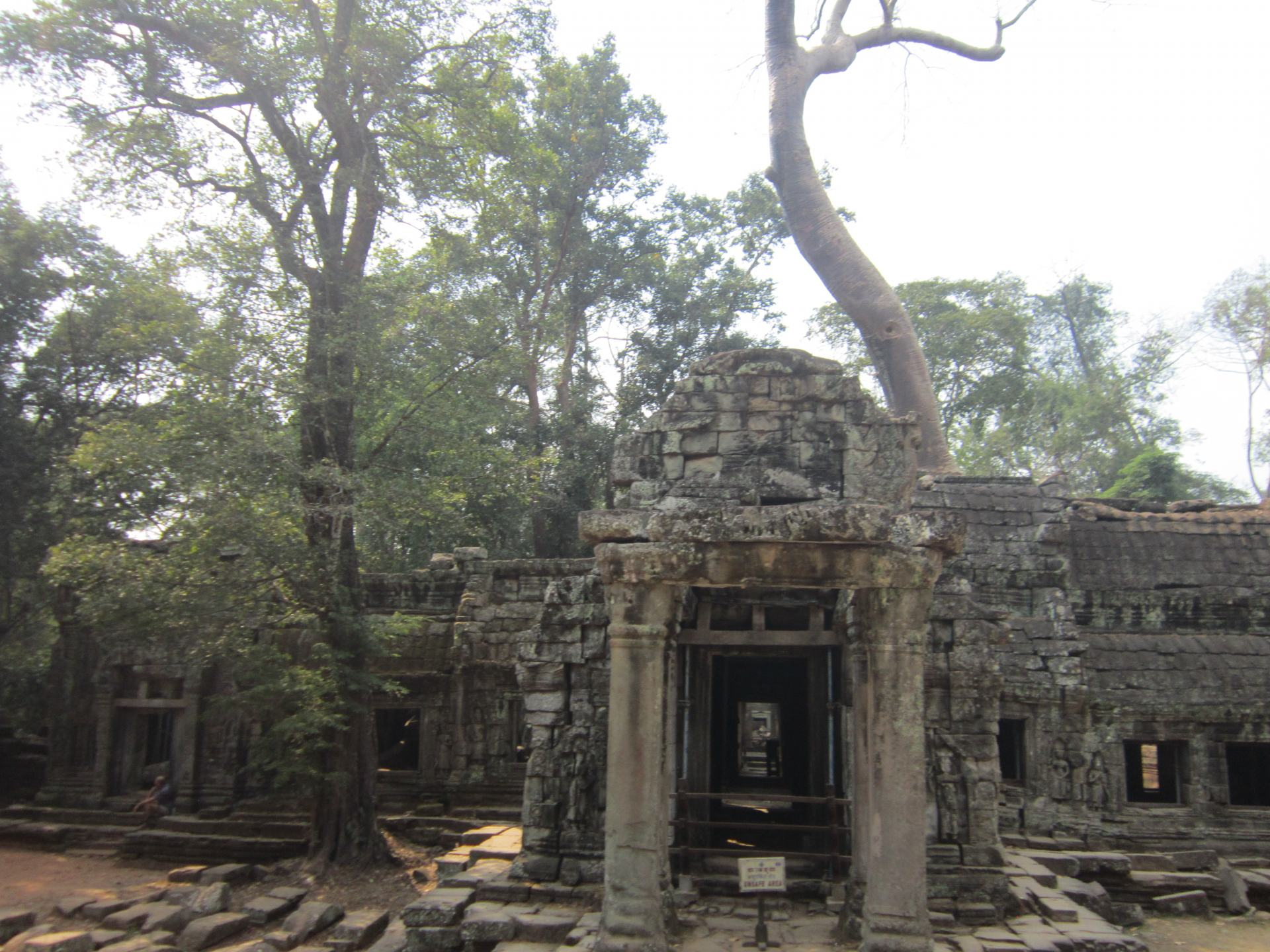 Some of the ruins of Ta Prohm, showing an doorway entrance and tree's growing around the walls. Ta Prohm is one of the best temples to see when following this Cambodia Itinerary.