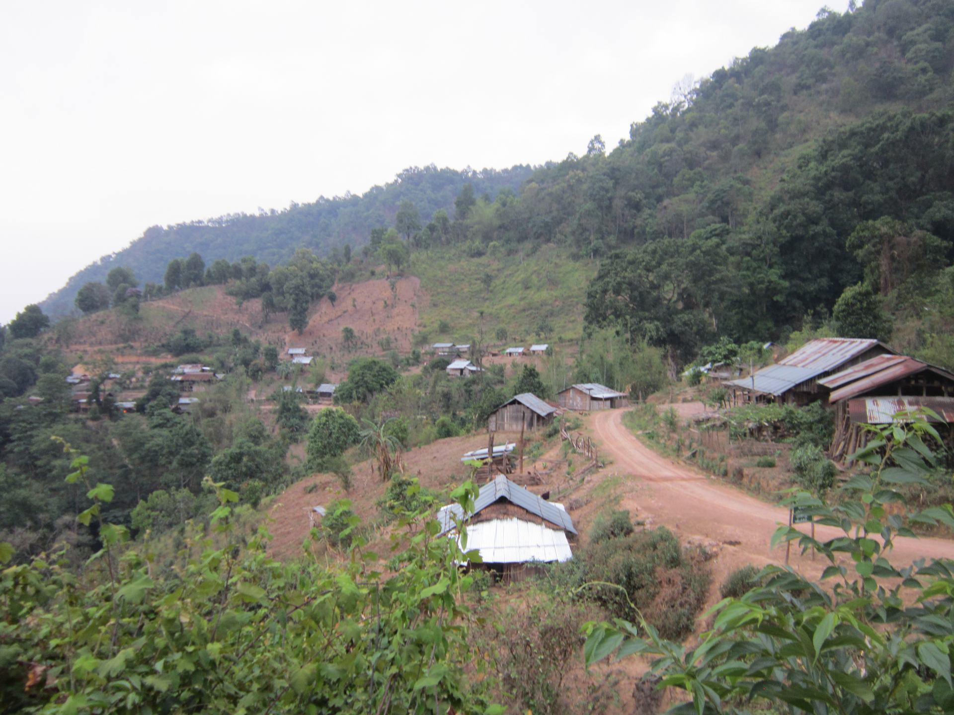 Several huts dotted around a mountain path, with trees around the sides