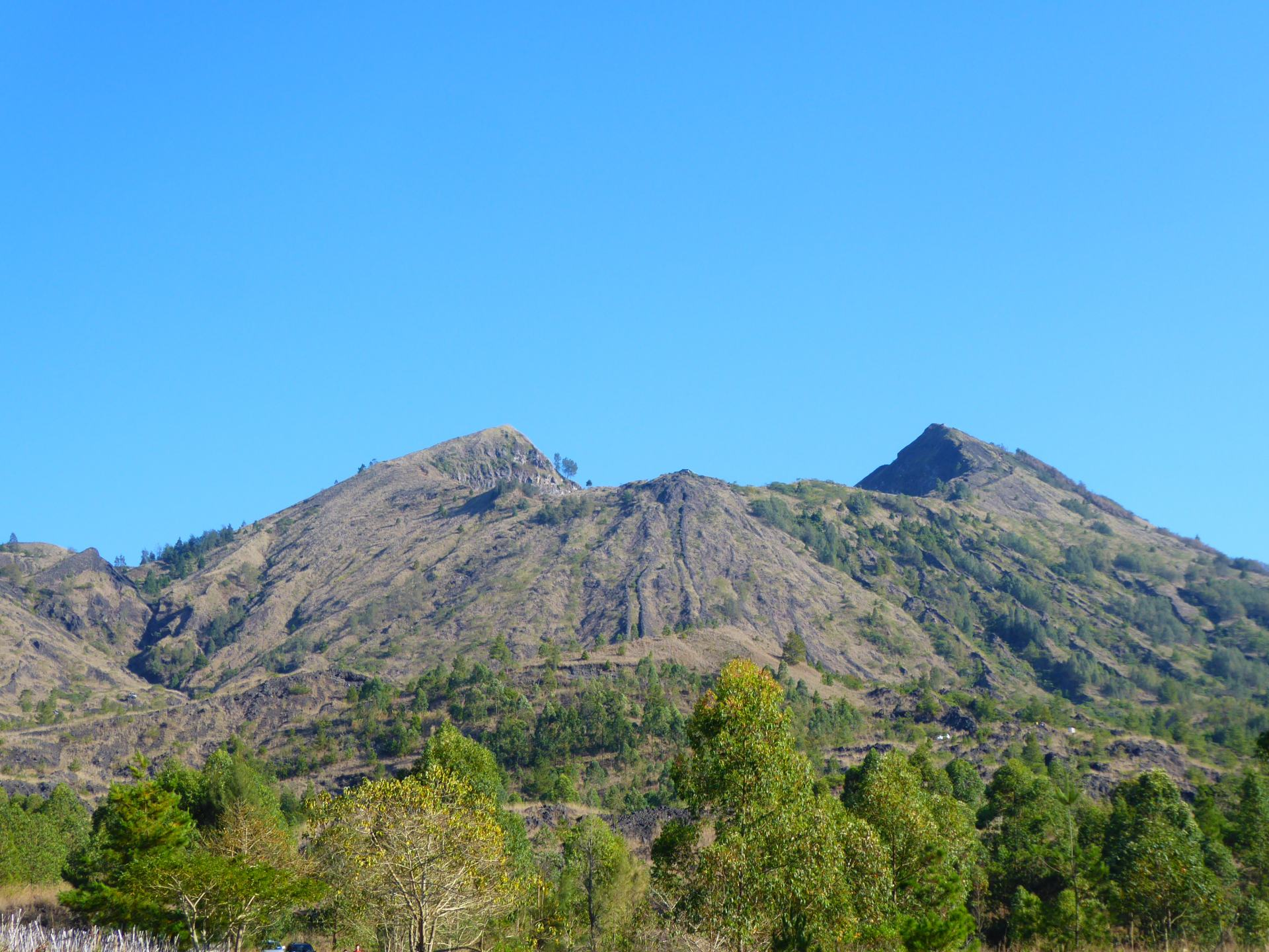 A view of the Mount Batur volcano, showing the crater, with greenery in the foreground and bright blue clear sky. One of the most popular treks in Southeast Asia.