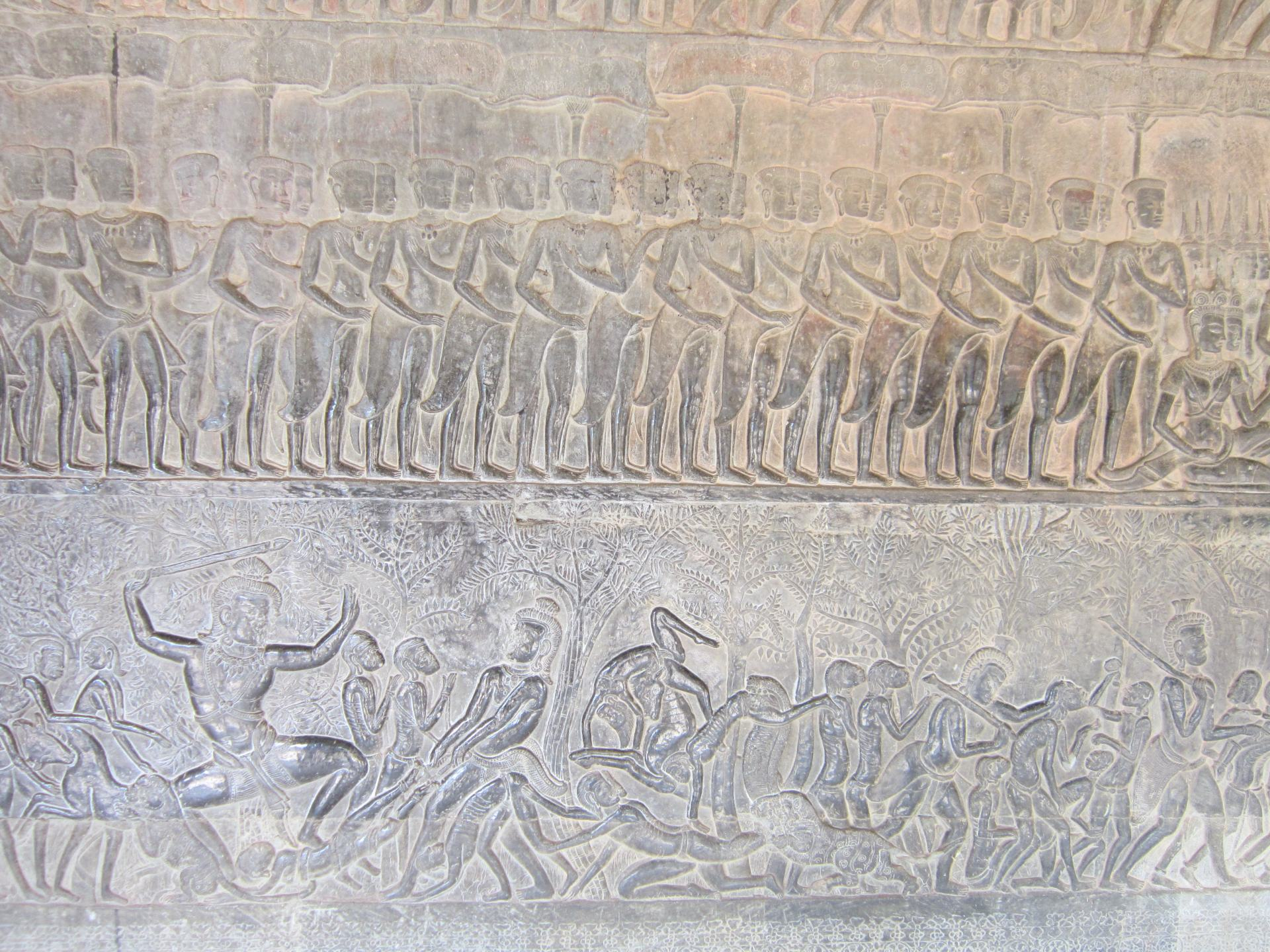 Hindu carvings inside Angkor Wat, showing many people in varying poses. There are 2 row,s the top row features people in a line, the bottom more sporadic.