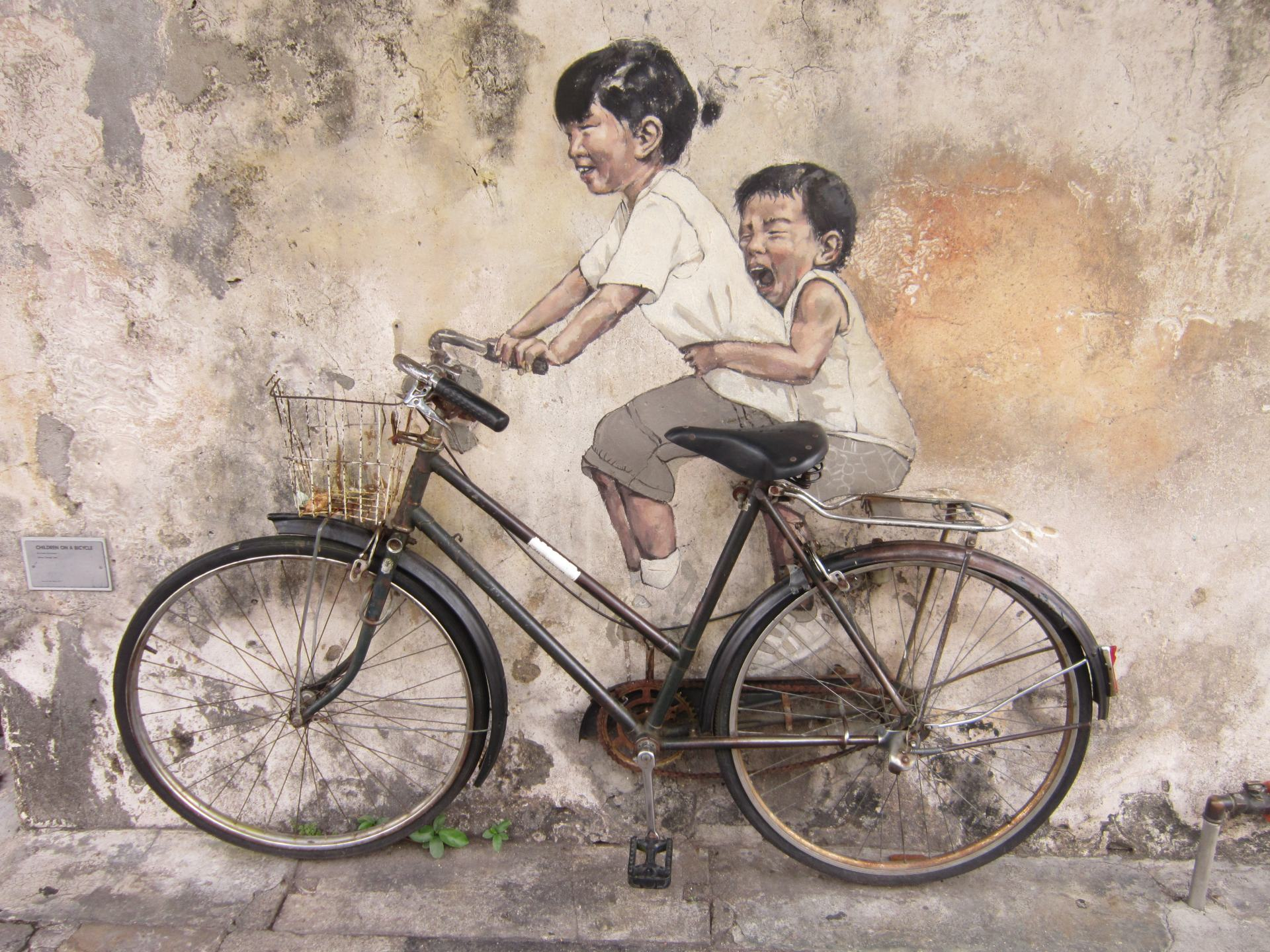 Street art of 2 children riding a bike in George Town. Its one of the best cities in Southeast Asia to see street art. The bike is real, attached to the wall.