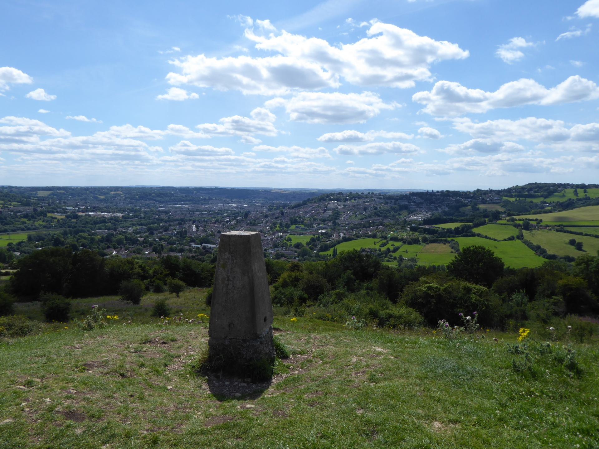 Looking over the city of Bath from the top of Solsbury Hill. A hill marker is in the foreground.
