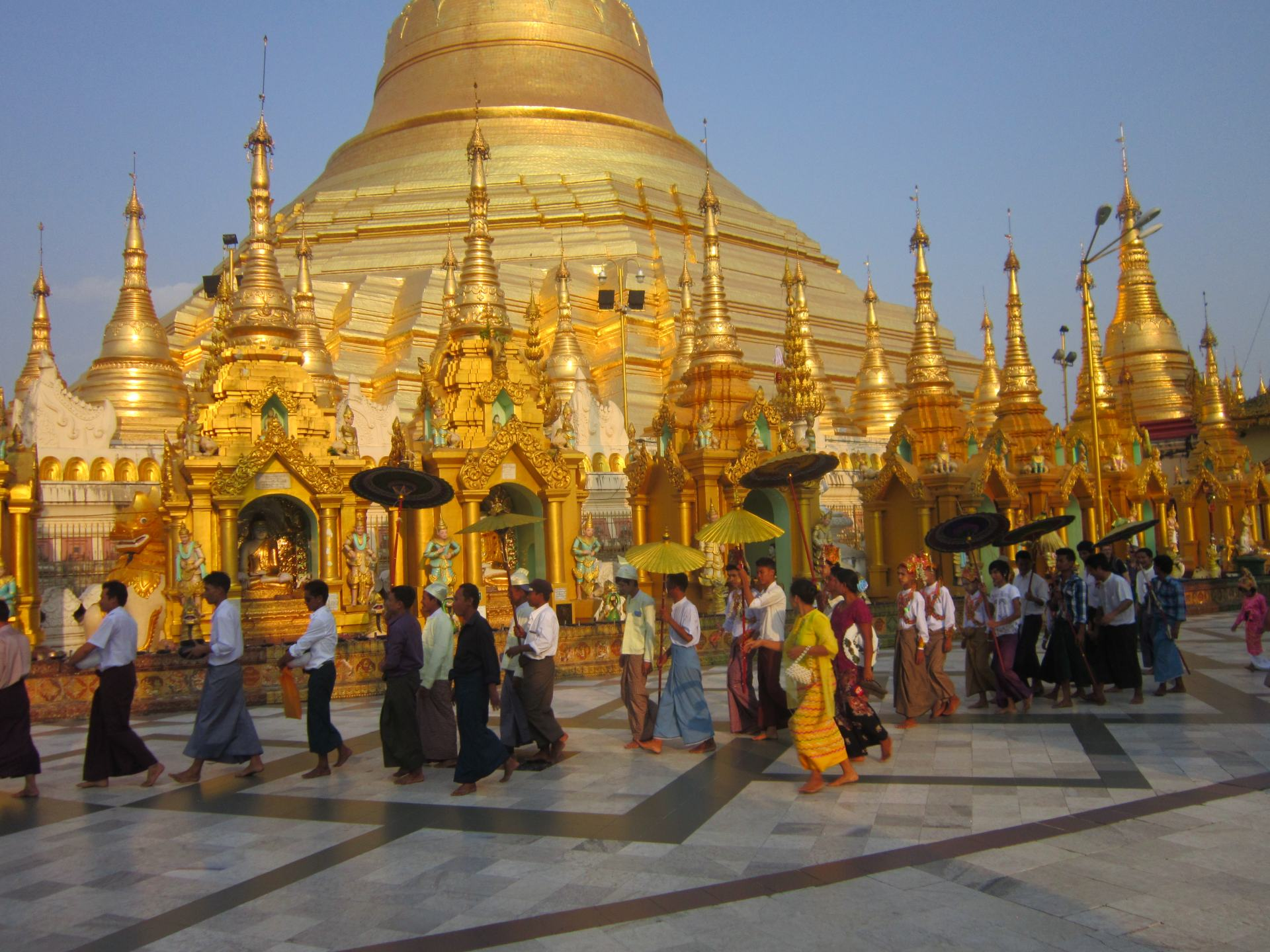 A crowd of people walking in front of the Golden Shwedagon Pagoda. One of the largest Southeast Asian temples.
