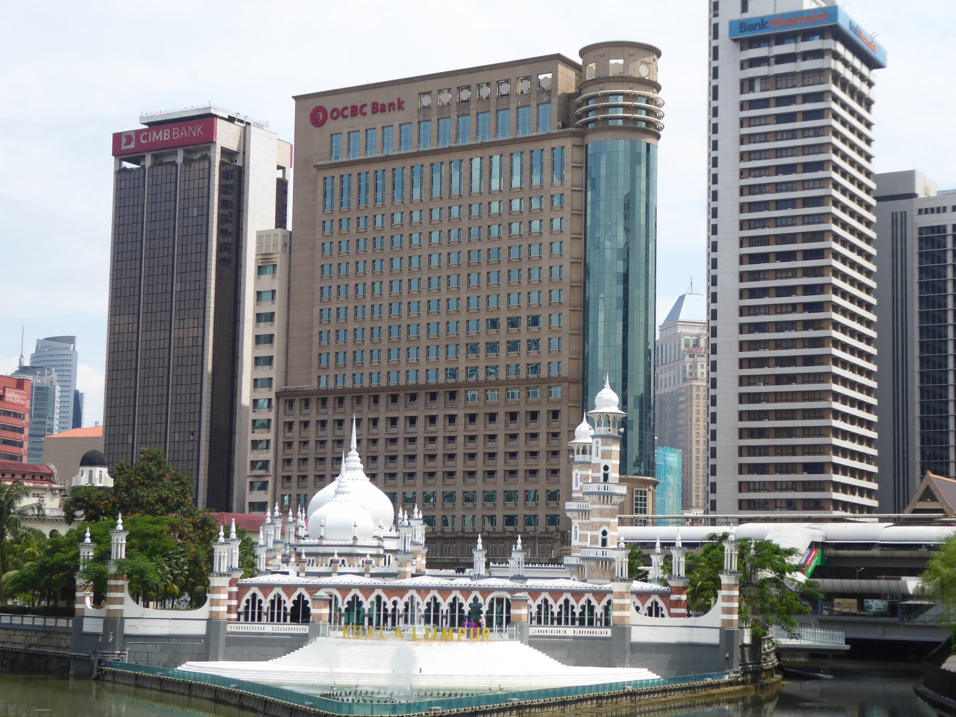 A view of the Masjid Japmek temple in Kuala Lumpur, with sky scrapers behind it.
