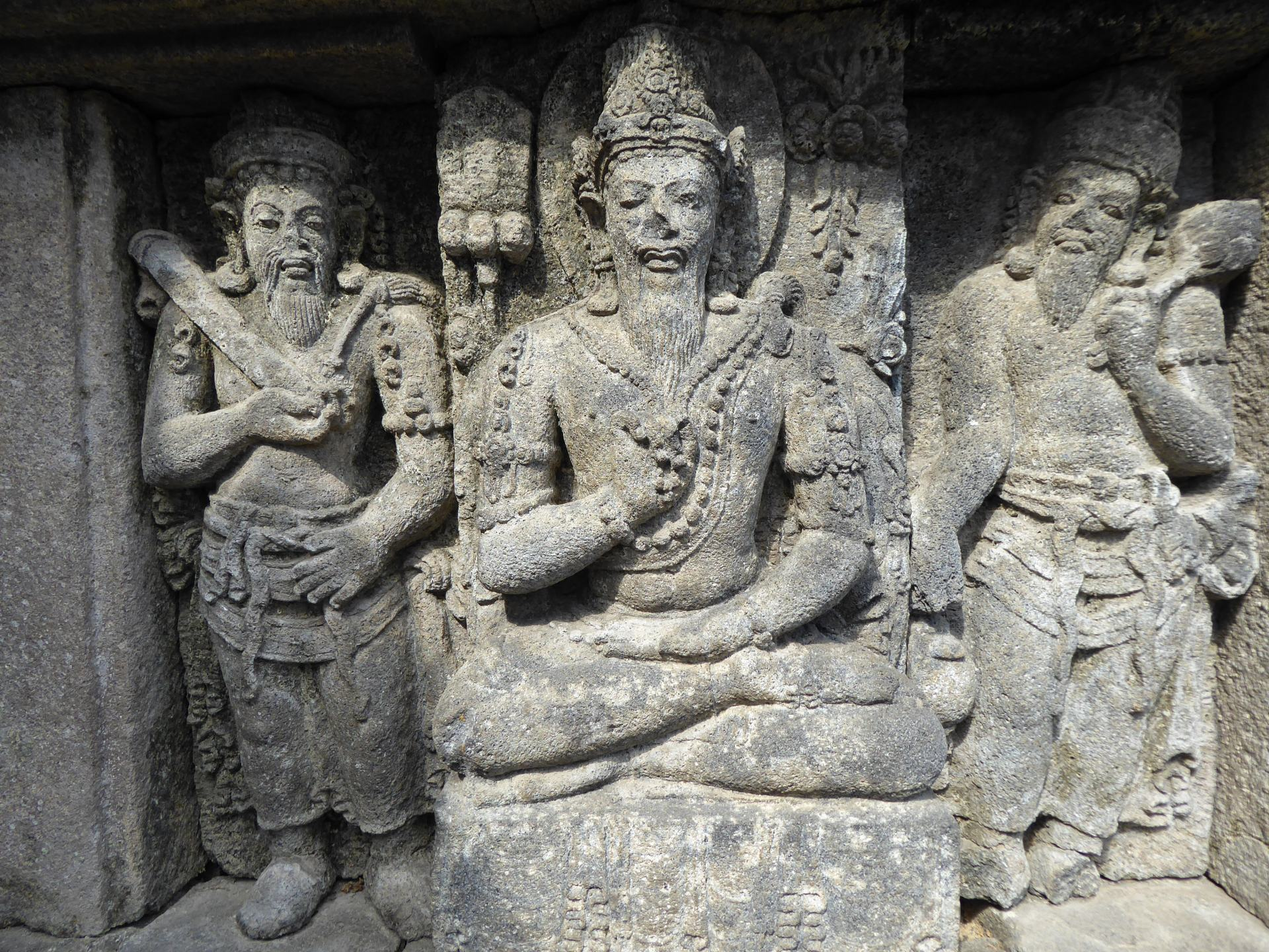 Stone carving of 3 Hindu figures at Prambanan, one of the Southeast Asian temples on this list.
