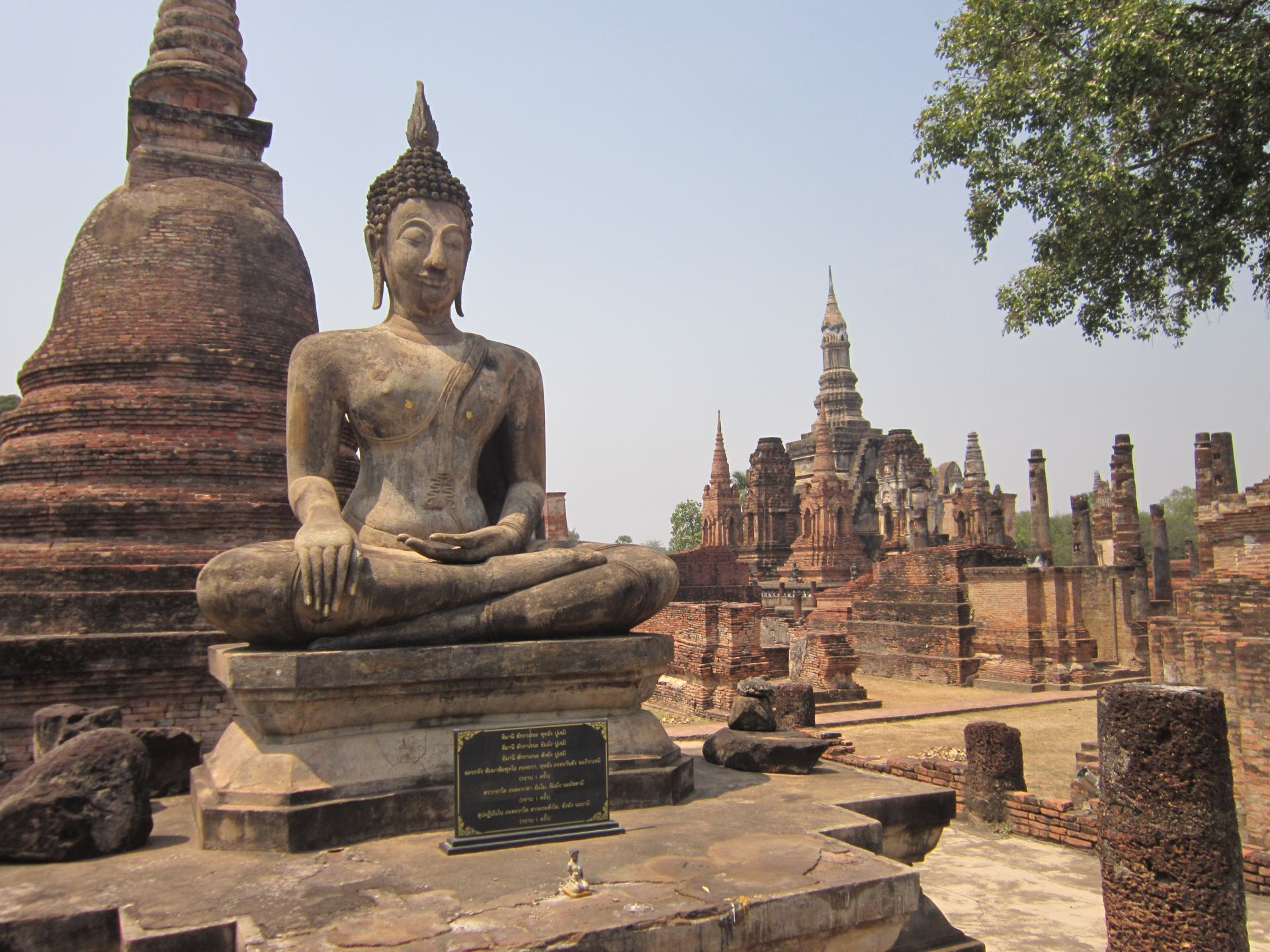 A large statue of a sitting Buddha in Sukhothai Historical Park, with other Buddhist style Southeast Asian temples and pillars around.