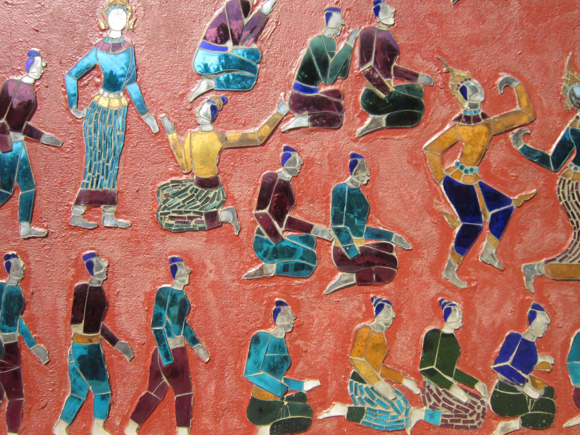 Artwork at Wat Xieng Thong Sim of colourful human figures in various poses, with a red background. One of the Southeast Asian temples really worth visiting.