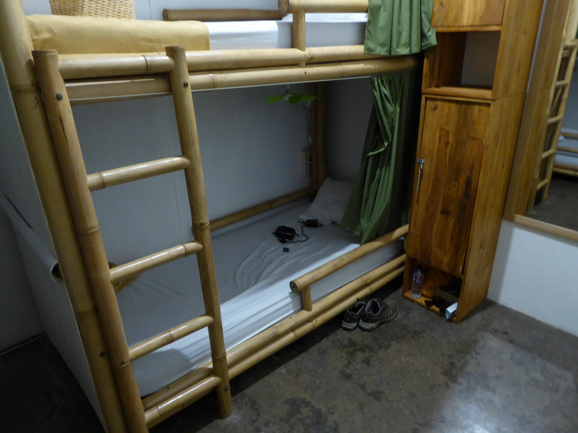 A view of a bottom bun bed in a hostel. A good Southeast Asia backpacking tip is to get sleep in beds with a curtain for privacy, which can be seen in the photo.