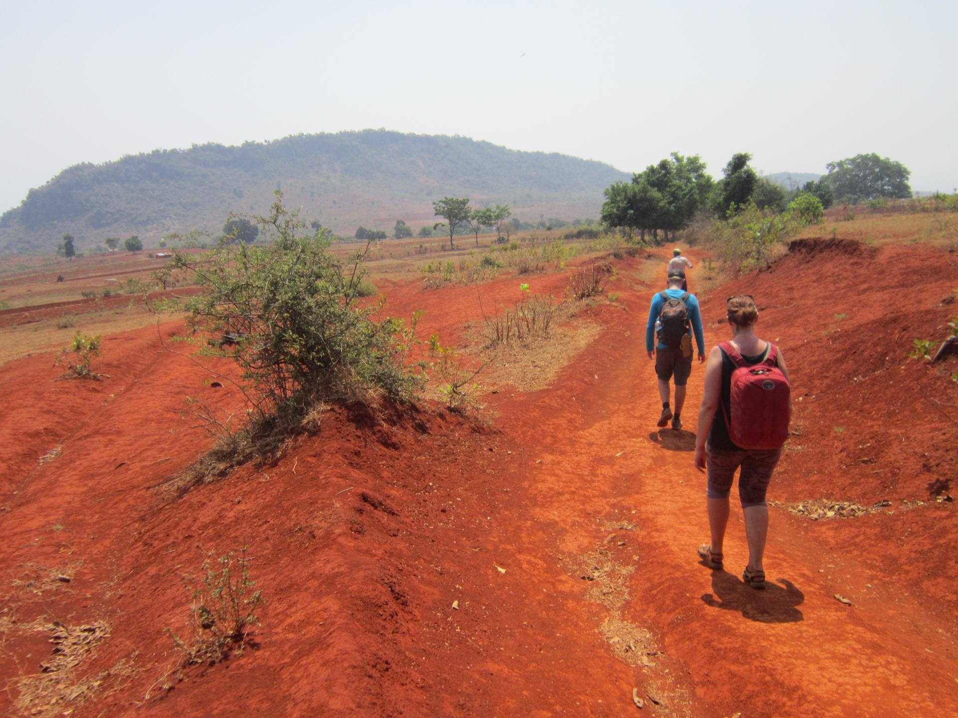 One of my big Southeast Asia backpacking tips is to go trekking. This shows people trekking across the red terrain of Myanmar's Shan State