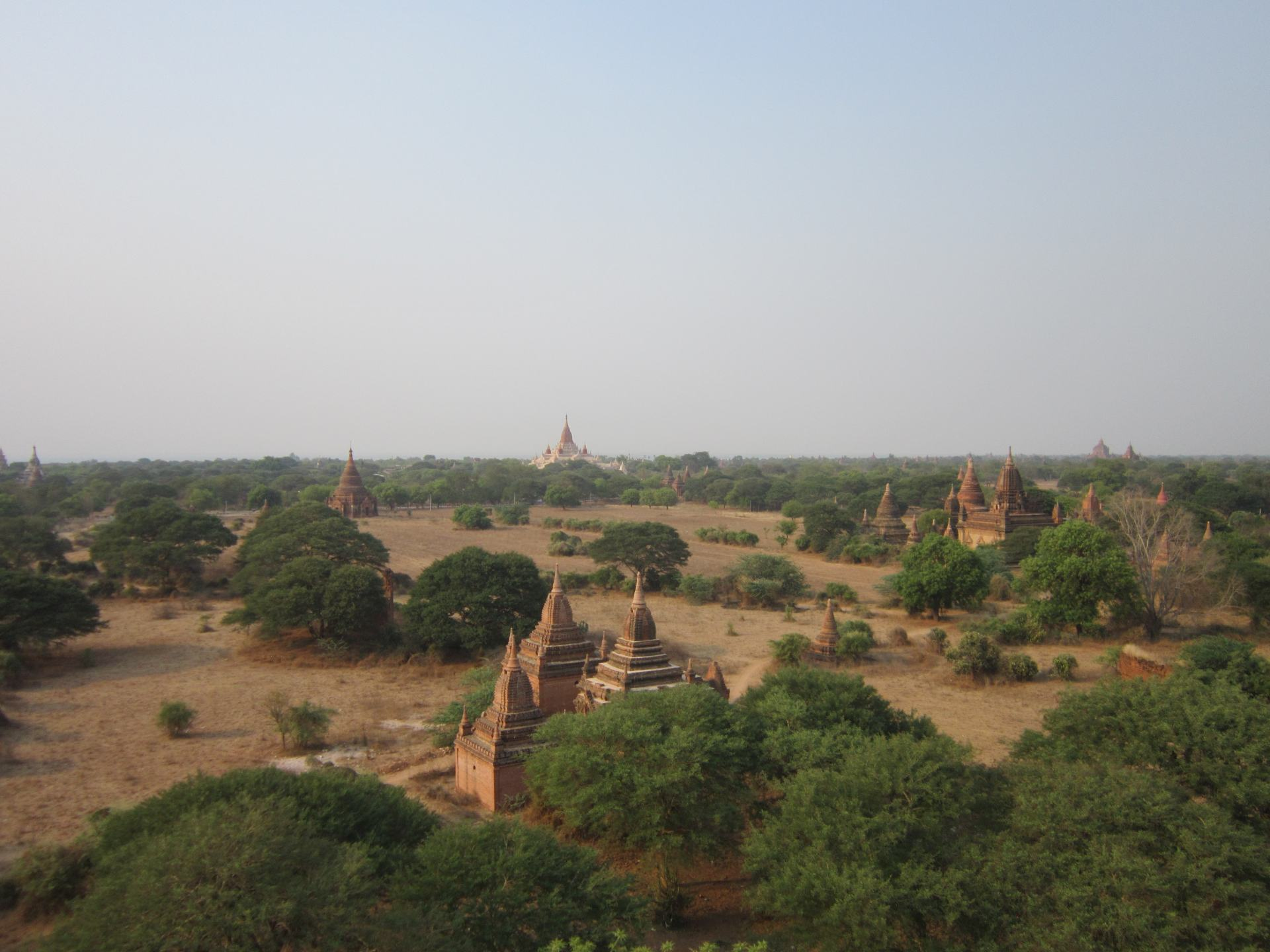 A view of Bagan showing temples, tree's and dusty ground. Demonstrating for these Southeast Asia backpacking tips what Bagan looks like in hot season.