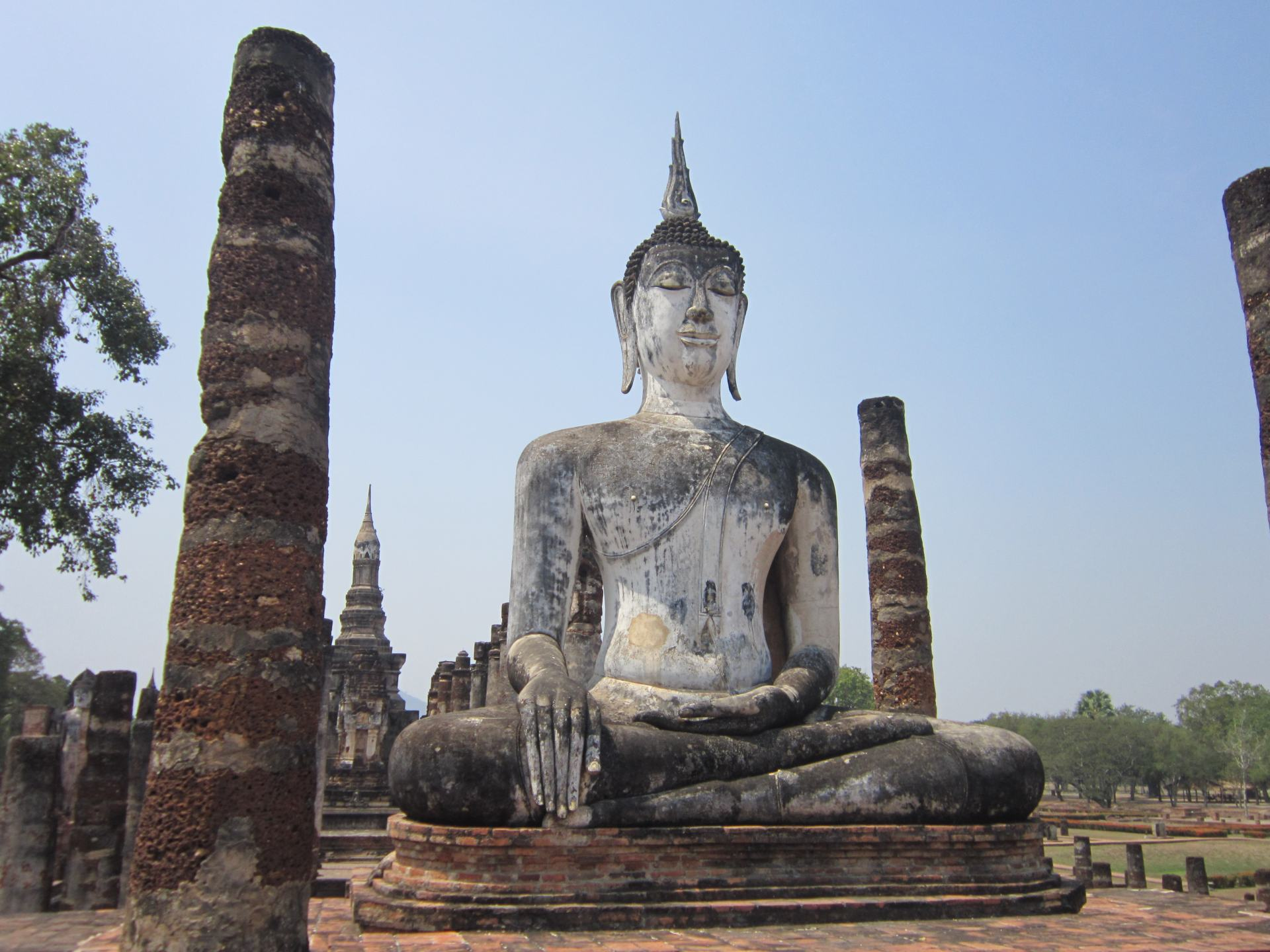 A statue of a meditating Buddha at the Sukhothai Historical Park. The statue is weathered ands there are several stone pillars in the picture too.