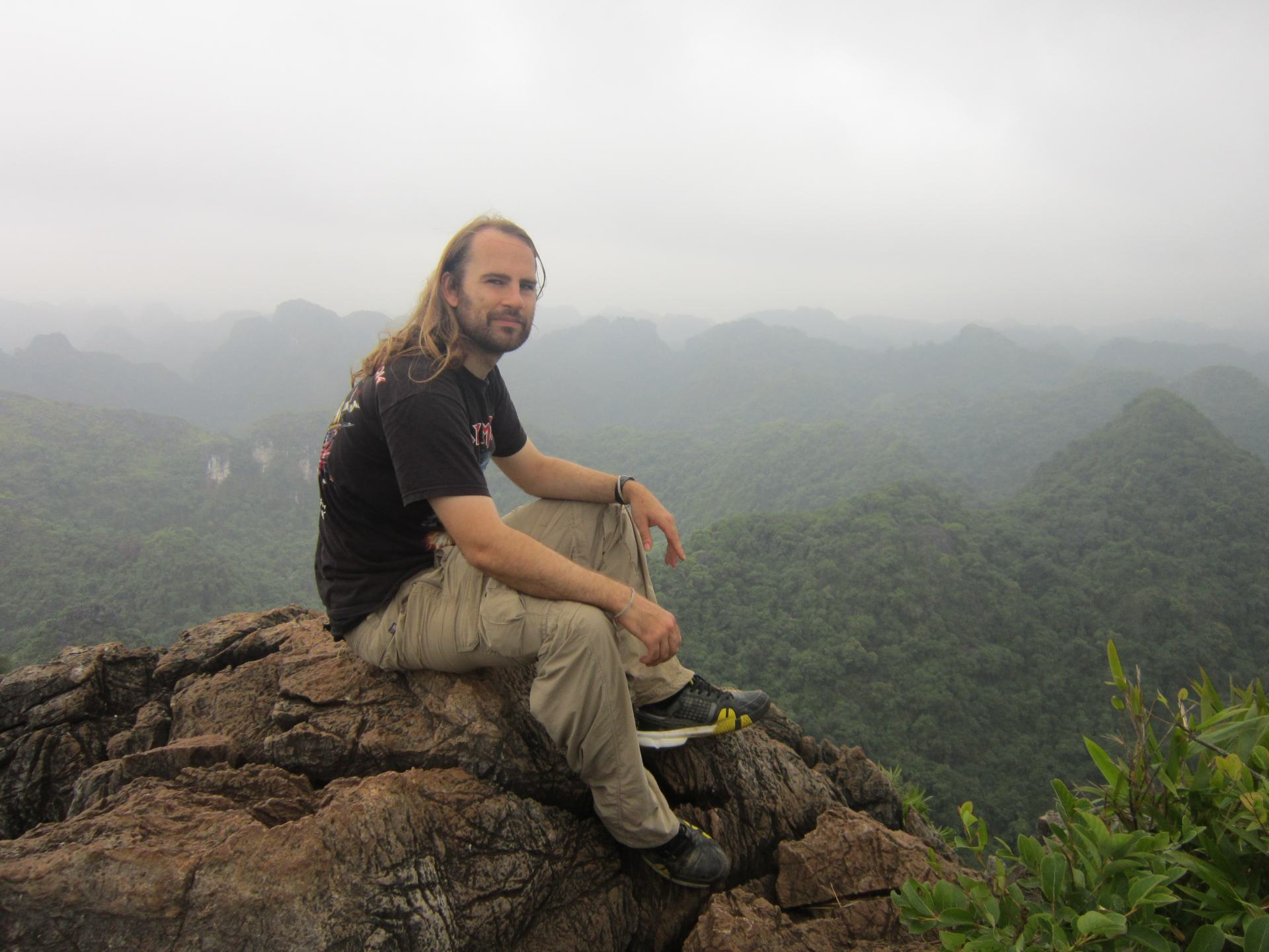 Dave Does the Travel Thing sat on rocks overlooking a misty jungle.