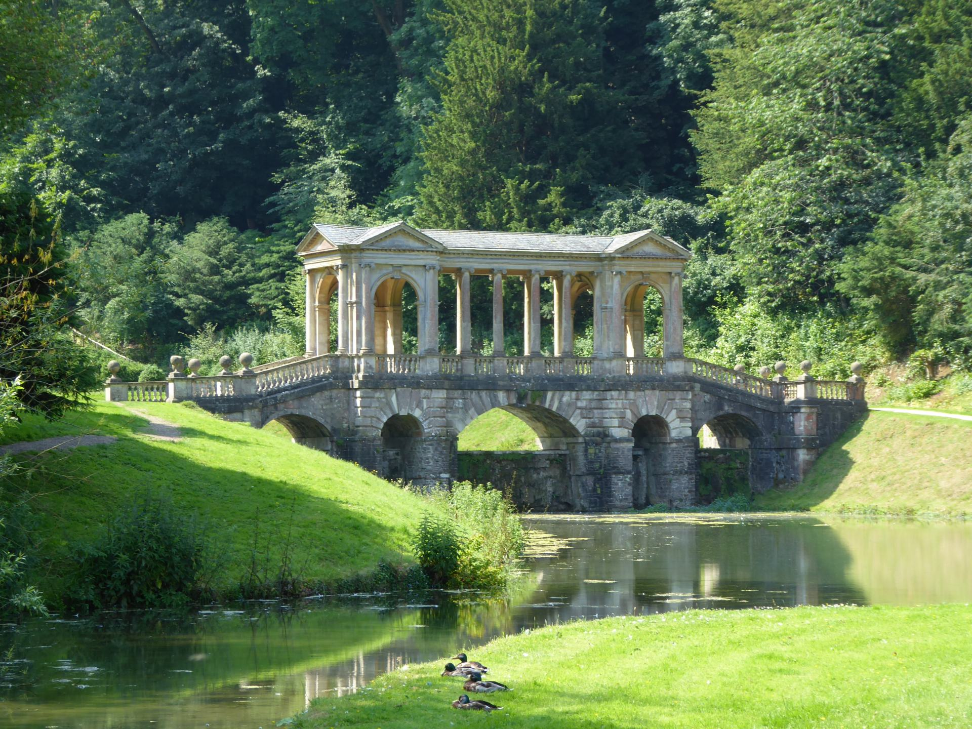 A bridge across water in Prior Park Landscape Garden, with tree's in the background. The bridge has several pillars holding up a roof. A few ducks sit on the grass in the foreground.