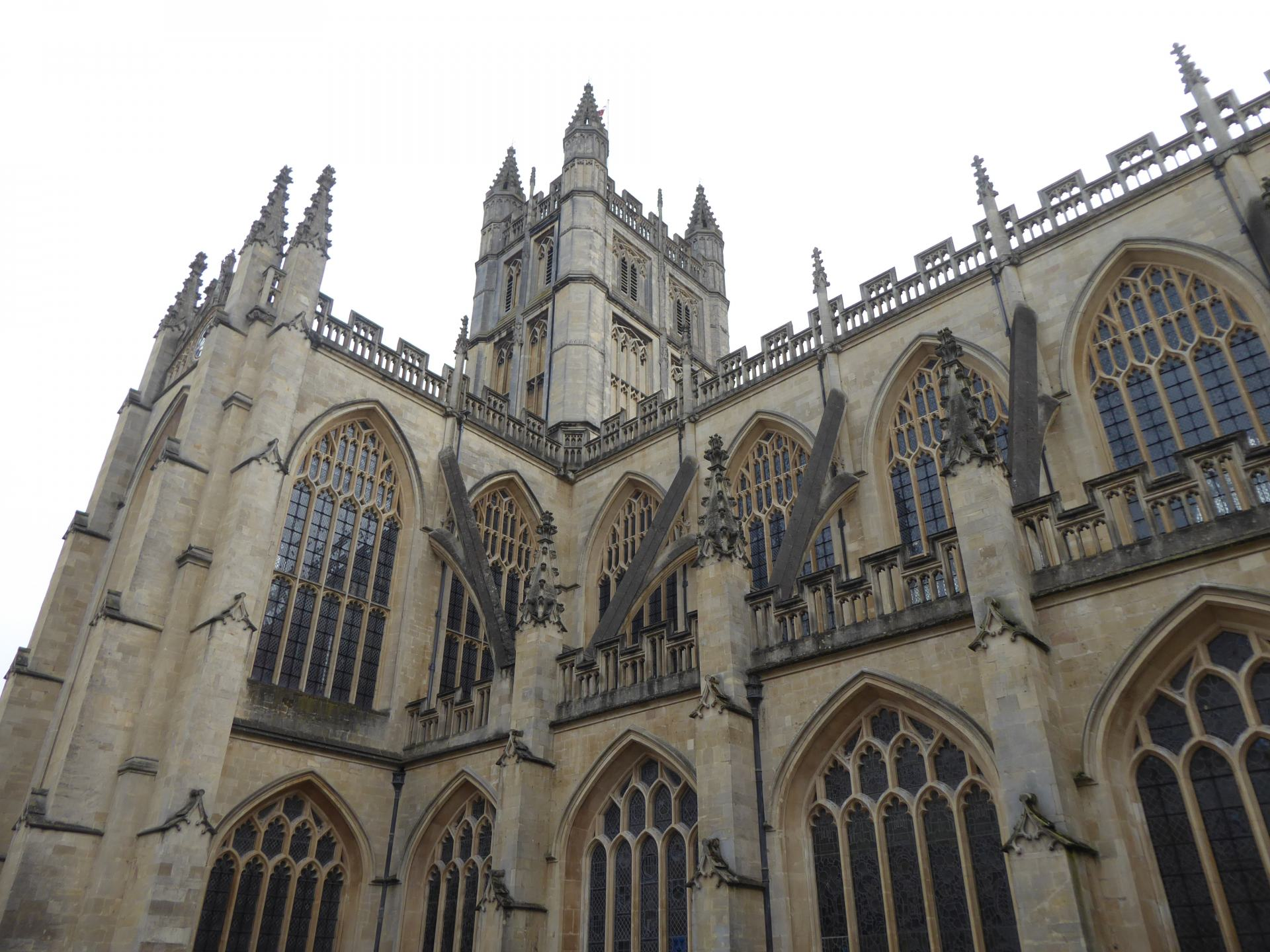 A view of the Bath Abbey from one if it's sides, showing it's tower and some of it's many windows.