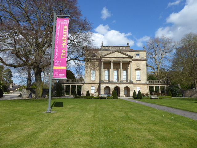 A view of the museum from the front, with a green lawn and a tree to the left and in the background of the right. A banner says the name 'The Holburne'.