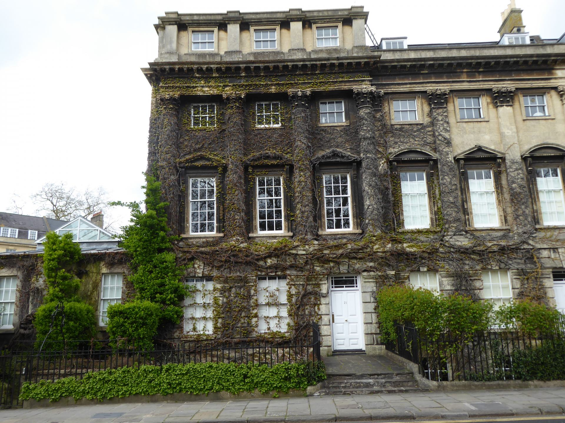 A building on the corner of Queens Square in Bath, with tree/plant roots growing over much of the stone.