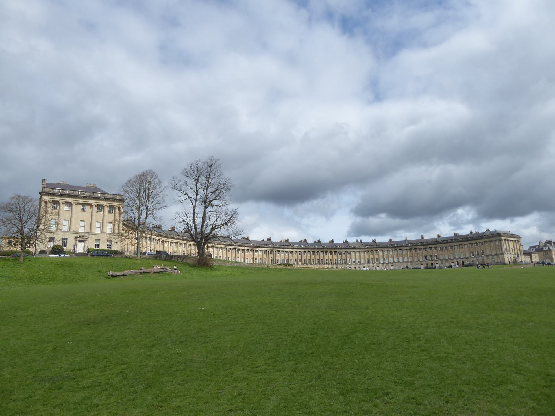 A view of the Royal Crescent in Bath, showing a Georgian building in a semi circle above a green area, with 3 tree's on the left.