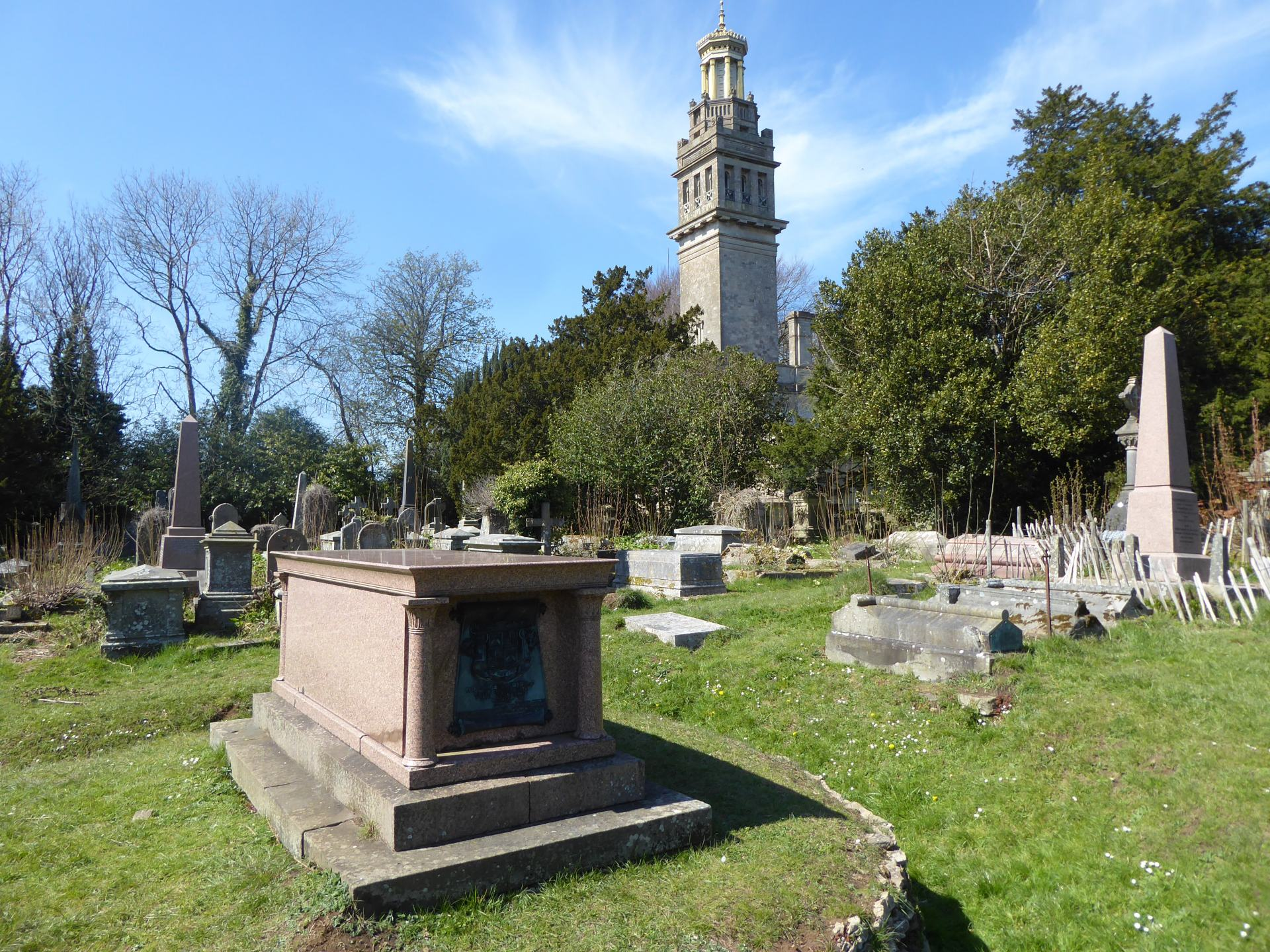 A view of a graveyard, with William Beckford's tomb in the foreground. Beckords Tower is in the background, rising above a cluster of tree's.