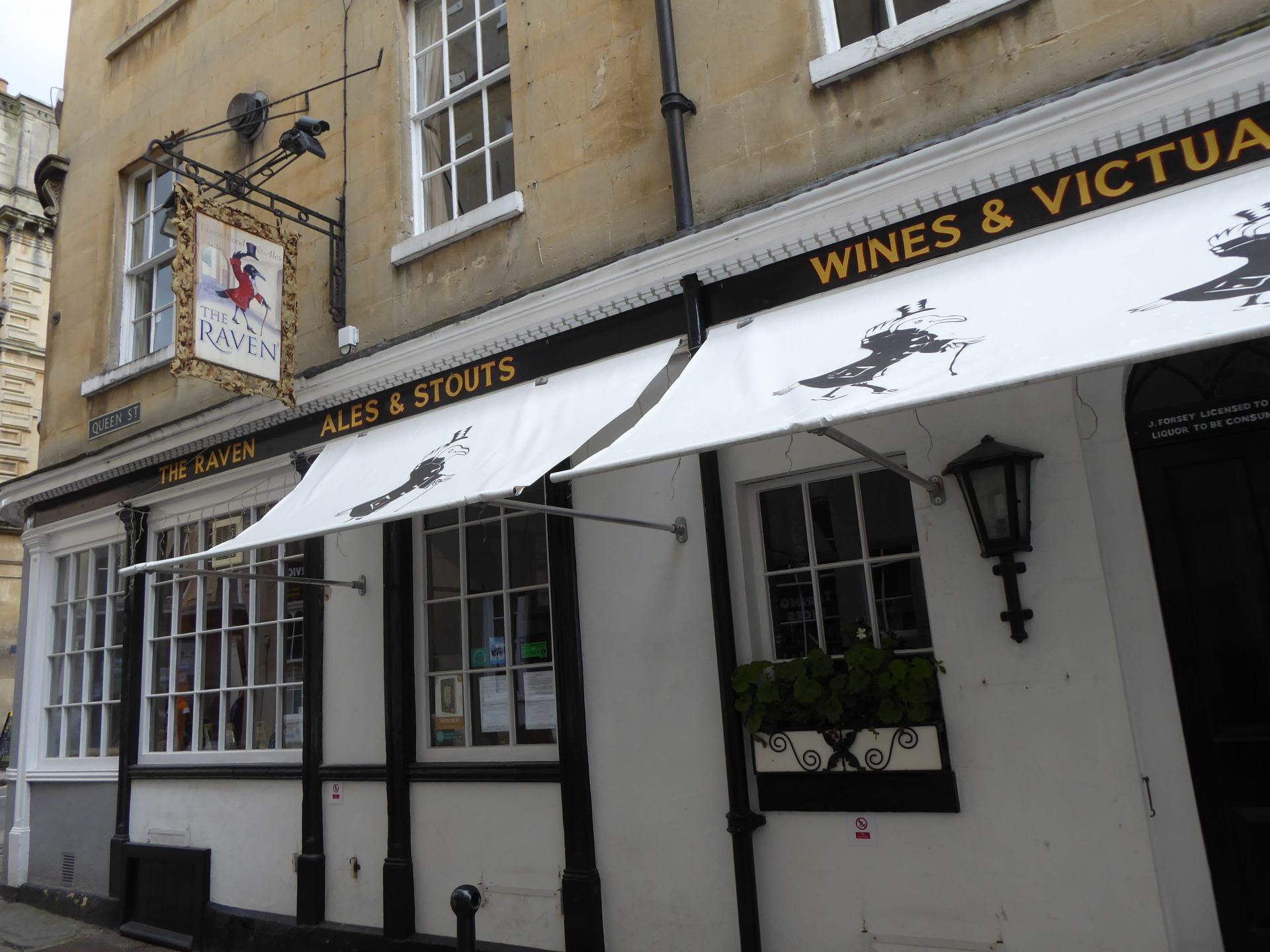 View of the outside of the Raven. Including it's pub sign saying 'The Raven' and text on the building including 'ALES & STOUTS'