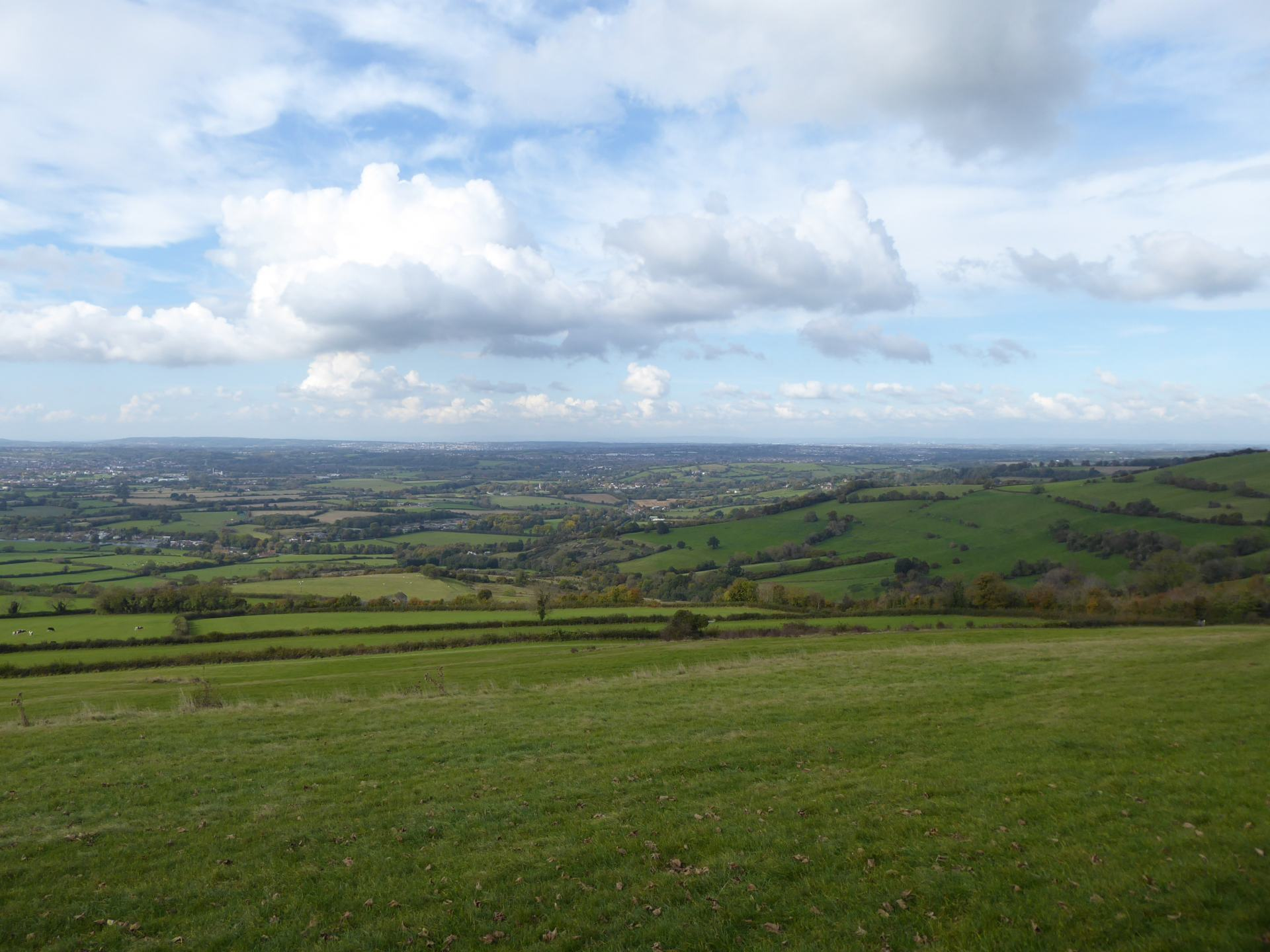 The view from Kelston Round Hill showing green fields with Bristol in the distance, and clouds above.