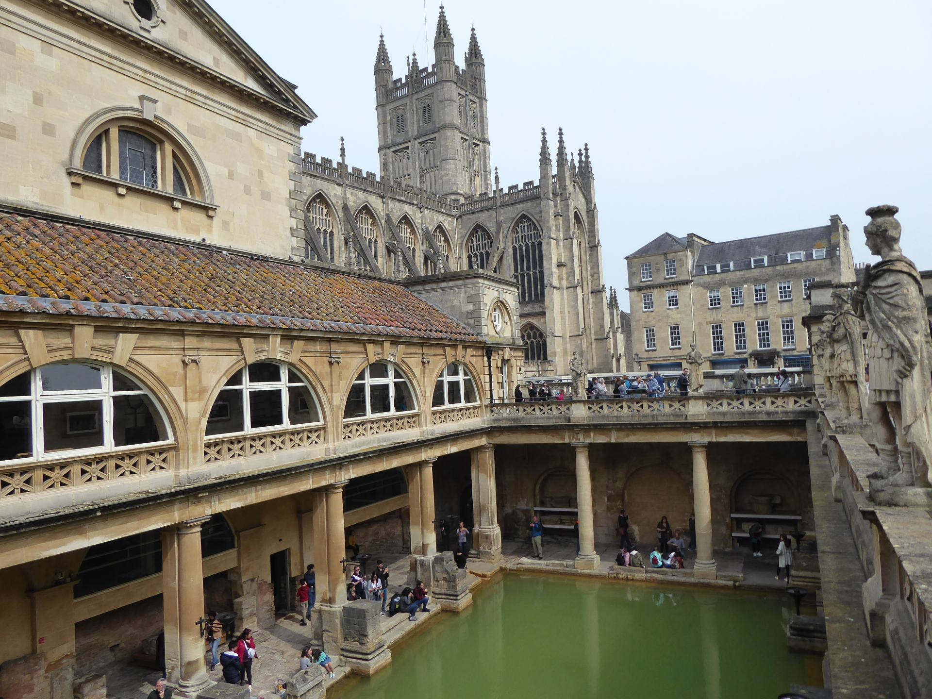 View from inside the Roman Baths showing green coloured water in the bottom of a pillared area. The Bath Abbey is the background above the baths.